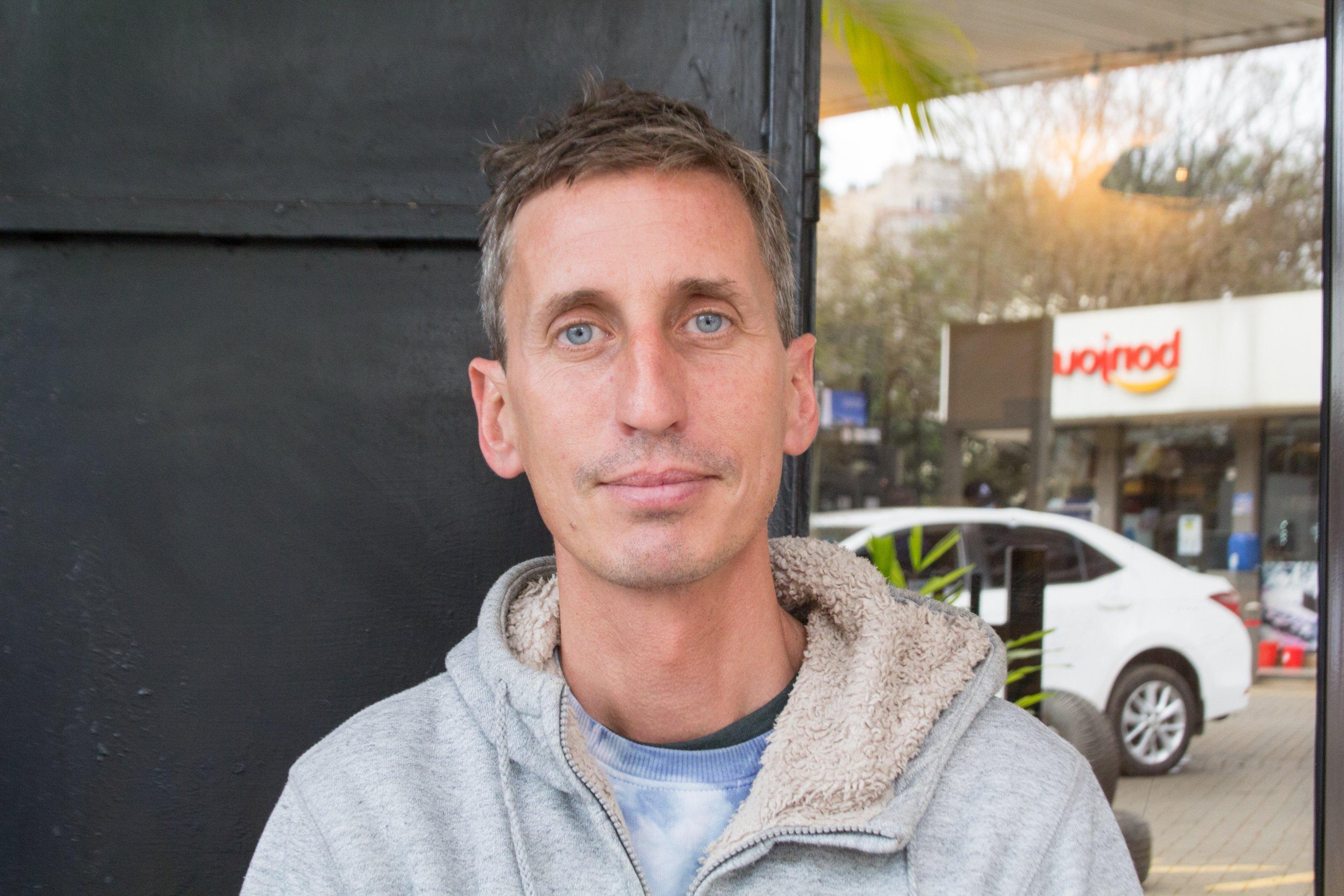 Ein Porträt von Sam Hopkins, einem Mann Ende 30, er trägt einen grauen Kapuzenpulli. Im Hintergrund spiegelt sich eine Tankstelle.