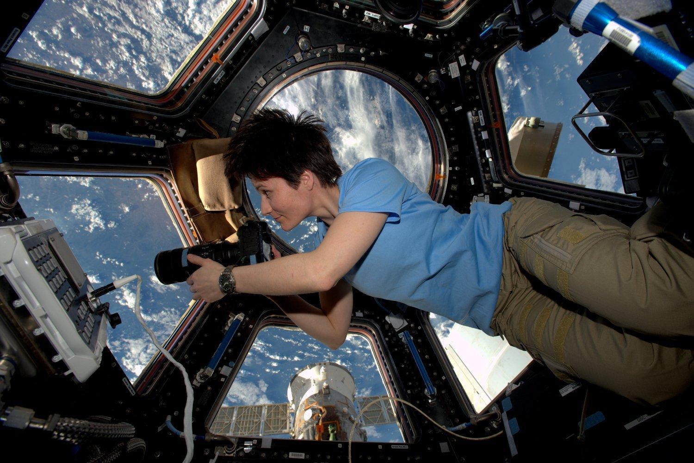 ESA-Astronautin Samantha Cristoforetti schwebt im Cupula-Modul der ISS, mit großen Fenstern und Erde im Hintergrund, hält eine große Kamera in der Hand und blickt konzentriert nach draußen.