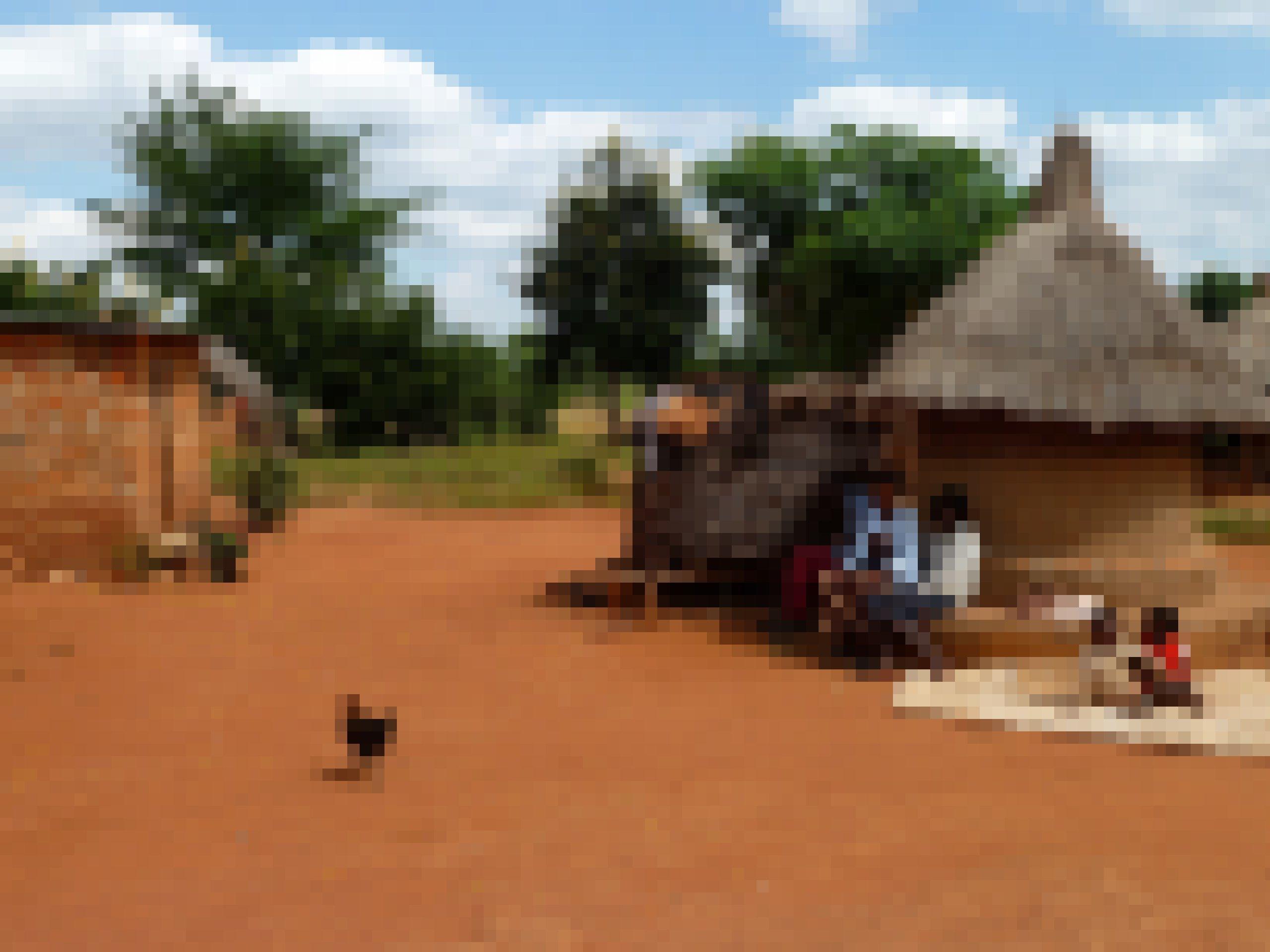 Frauen und Kinder sitzen vor einem grasgedeckten runden Lehmhäuschen, die Erde in dem Hof hat rötliche Farbe, ein Huhn rennt durch's Bild