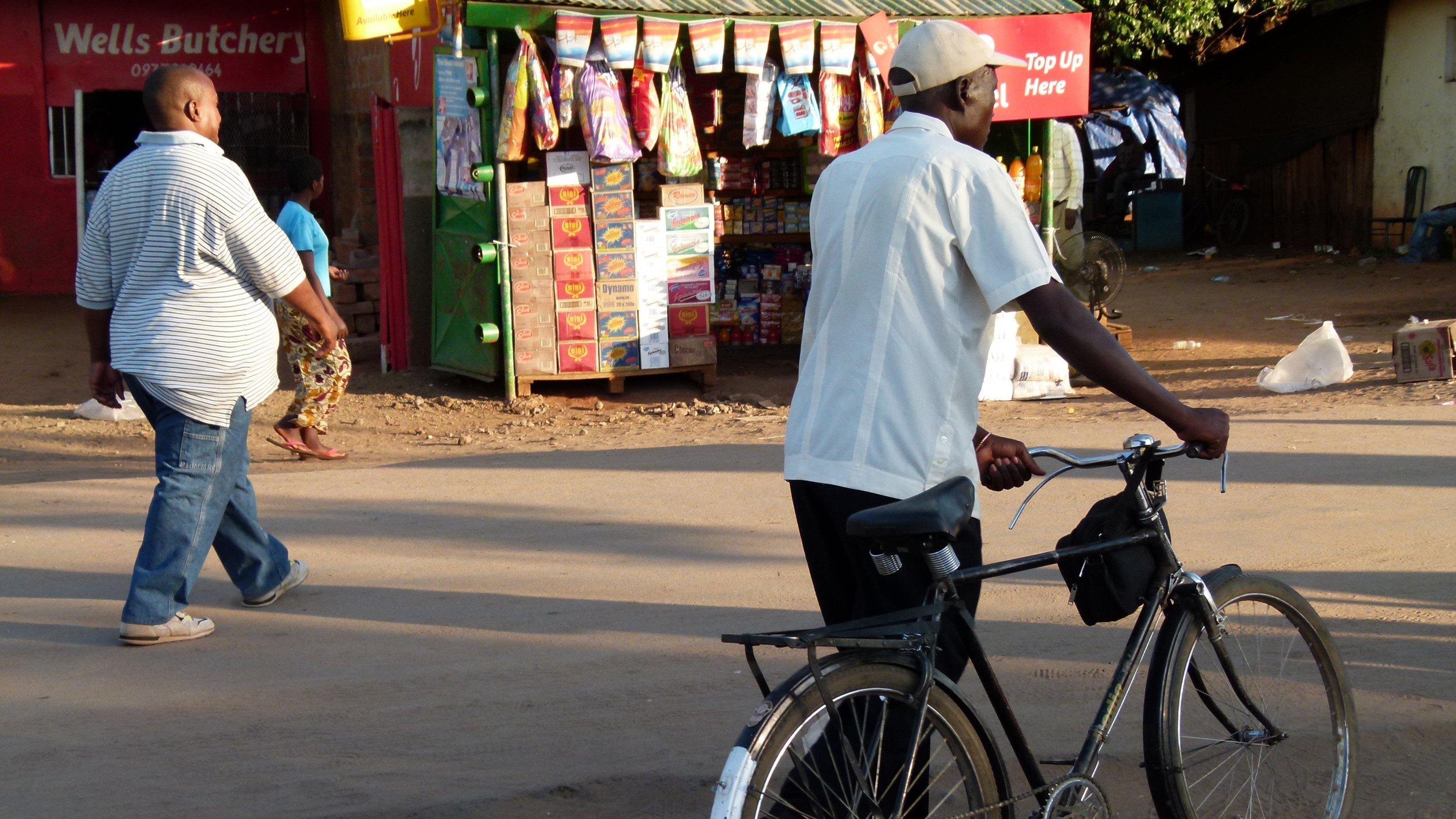 Straßenszene in Sambia: Zwei Fussgänger gehen an einem Markstand vorbei, einer schiebt sein Fahrrad