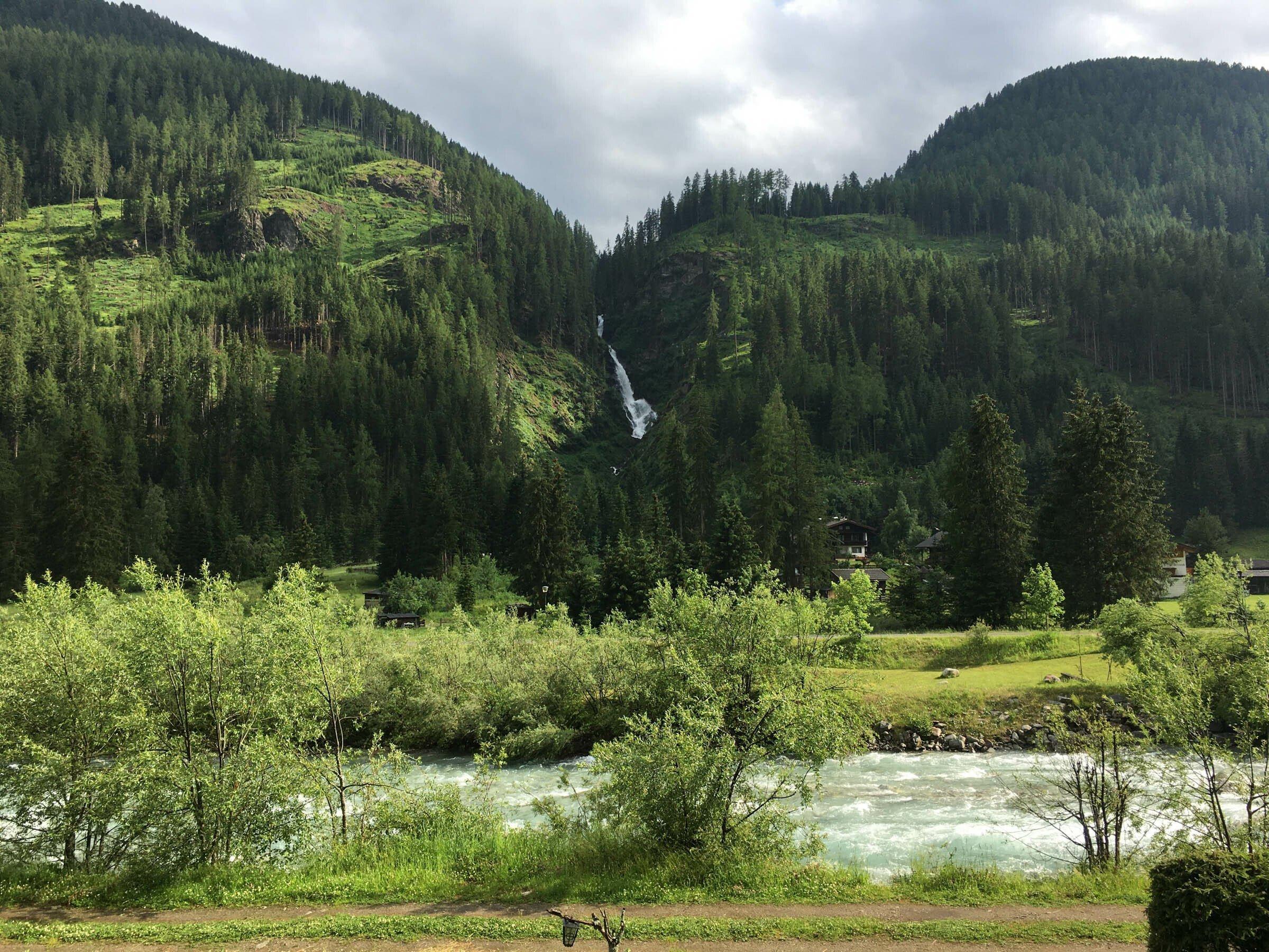 Quer im Bild ein Gebirgsbach mit Uferghölz, geradeaus Berge, Wald und ein hoher Wasserfall.