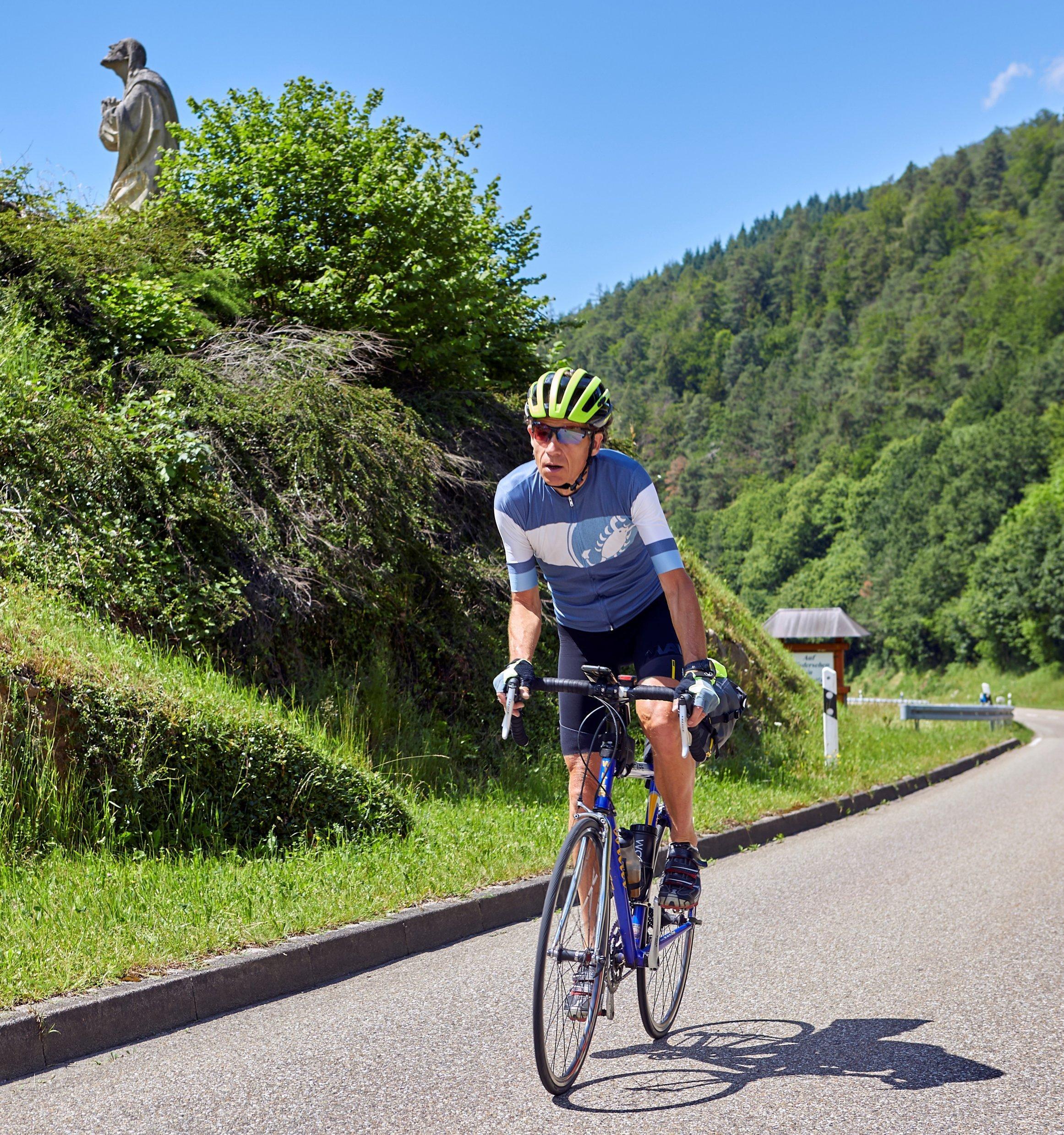 Martin C. Roos im Wiegetritt auf seinem Rennrad, im Hintergrund eine betende Steinfigur.