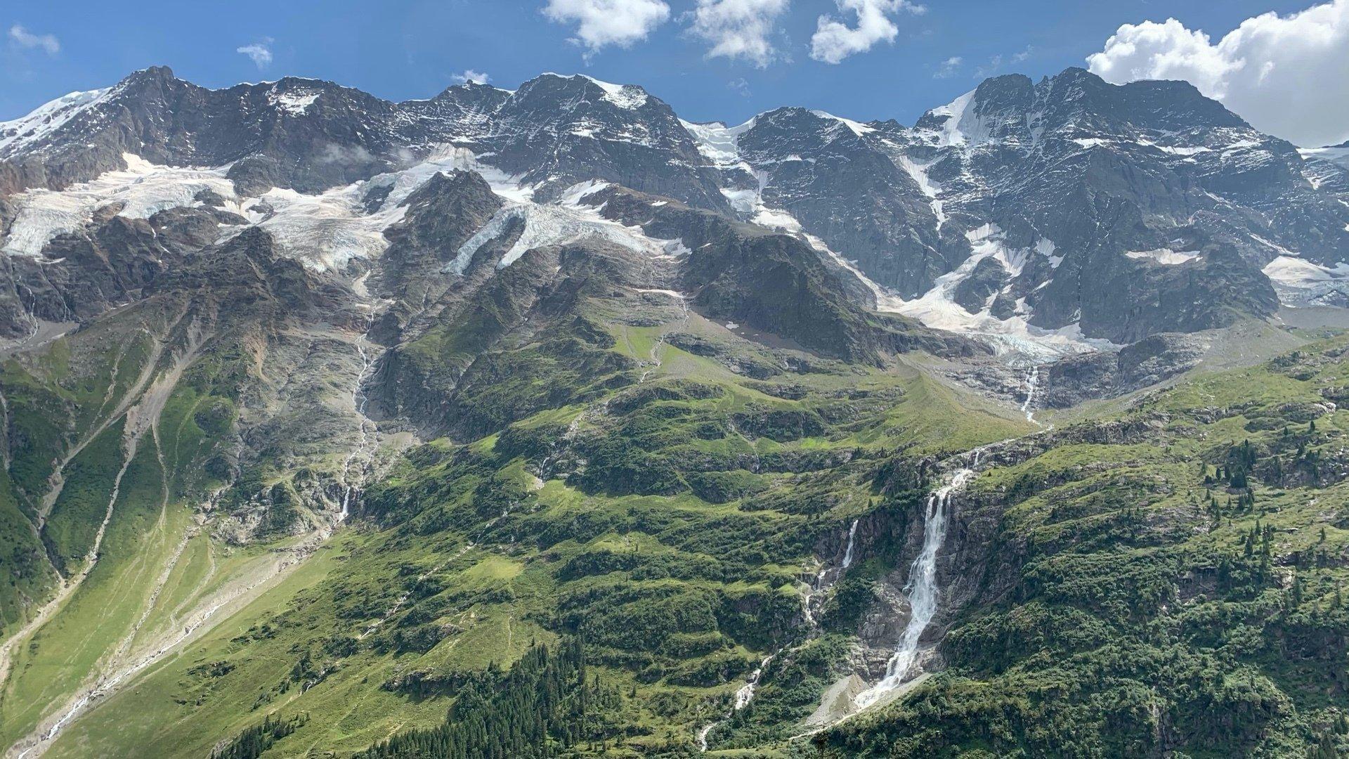 Schneebedeckte Berge ragen in den blauen Himmel. Die Vegetation verändert sich talabwärts von Gestein zu Wald- und Grünflächen. Mittig befindet sich ein Wasserfall.