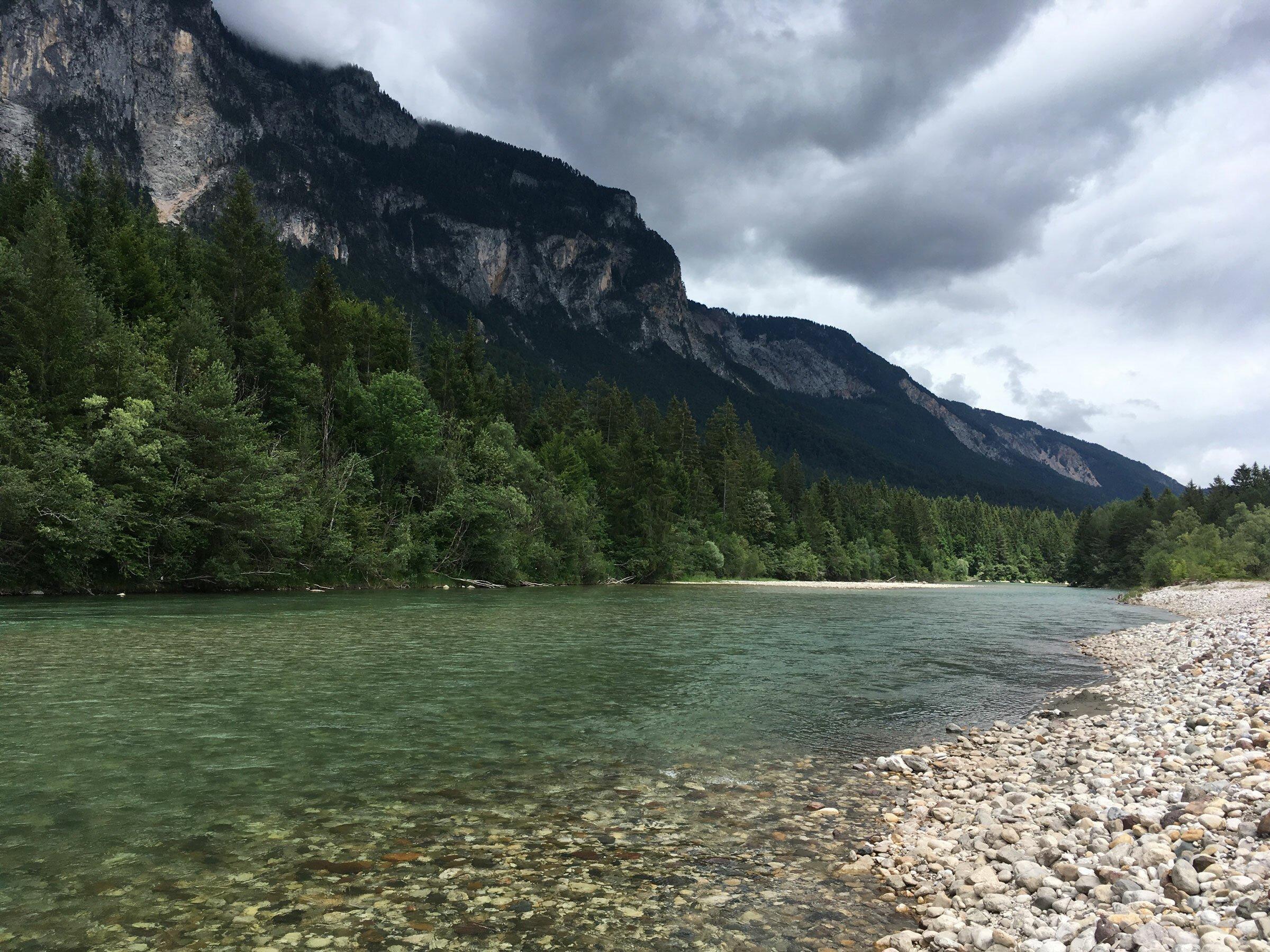 Links ragt ein Berg auf, davor ein Nadelwald und daneben ein dunkelgrüner Fluss mit Schotterufer.