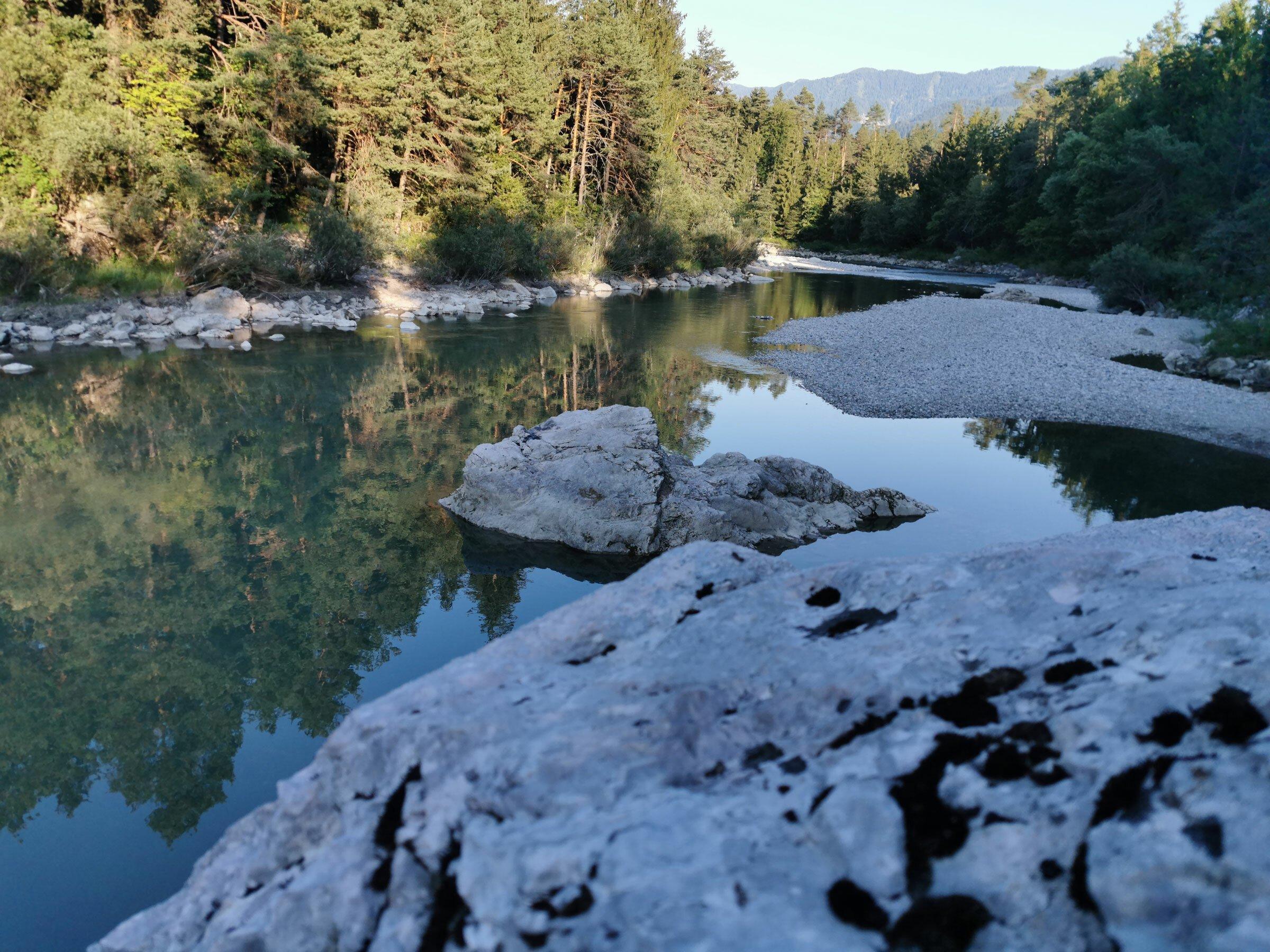 Nadelwald, dunkelgrünes Flusswasser, Schotterufer und große Steine.