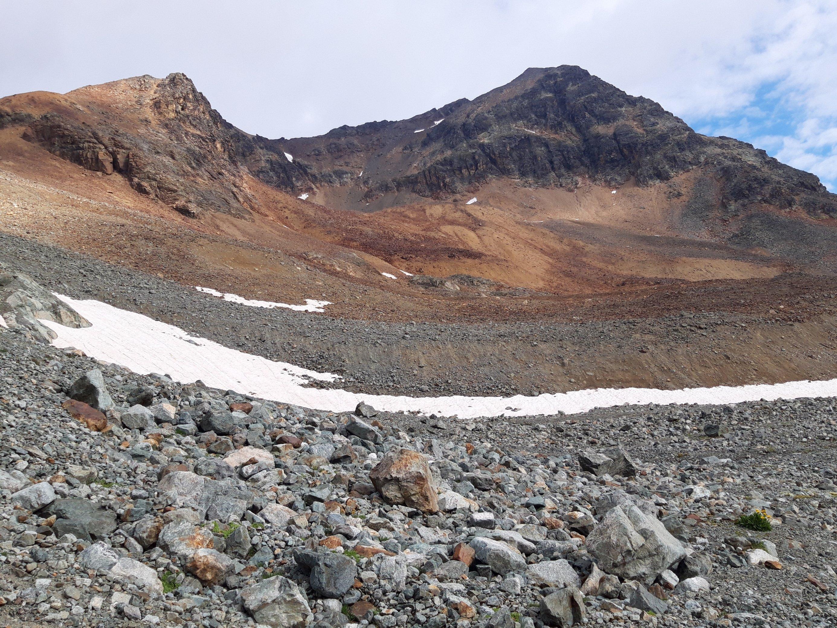 Wenige Schneereste und viel loses, braunes, rotes und ockerfarbenes Geröll an einem Berghang.