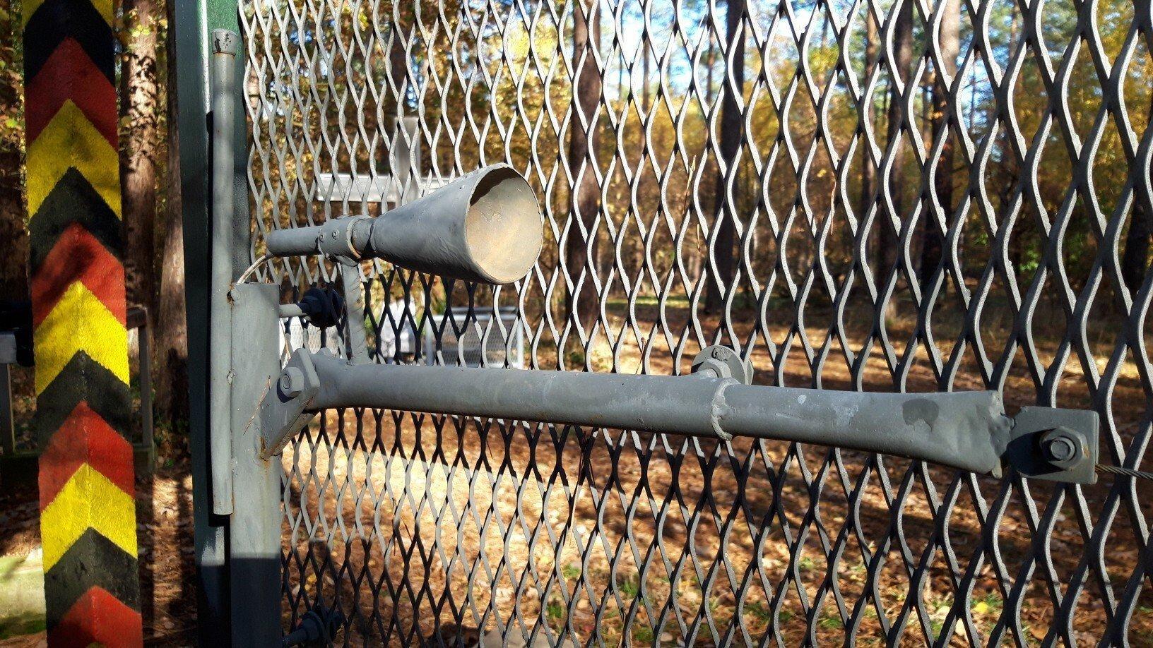 Neben einem alten DDR-Grenzpfosten steht ein Stück Zaun, an dem oben eine Selbstschussanlage montiert ist.