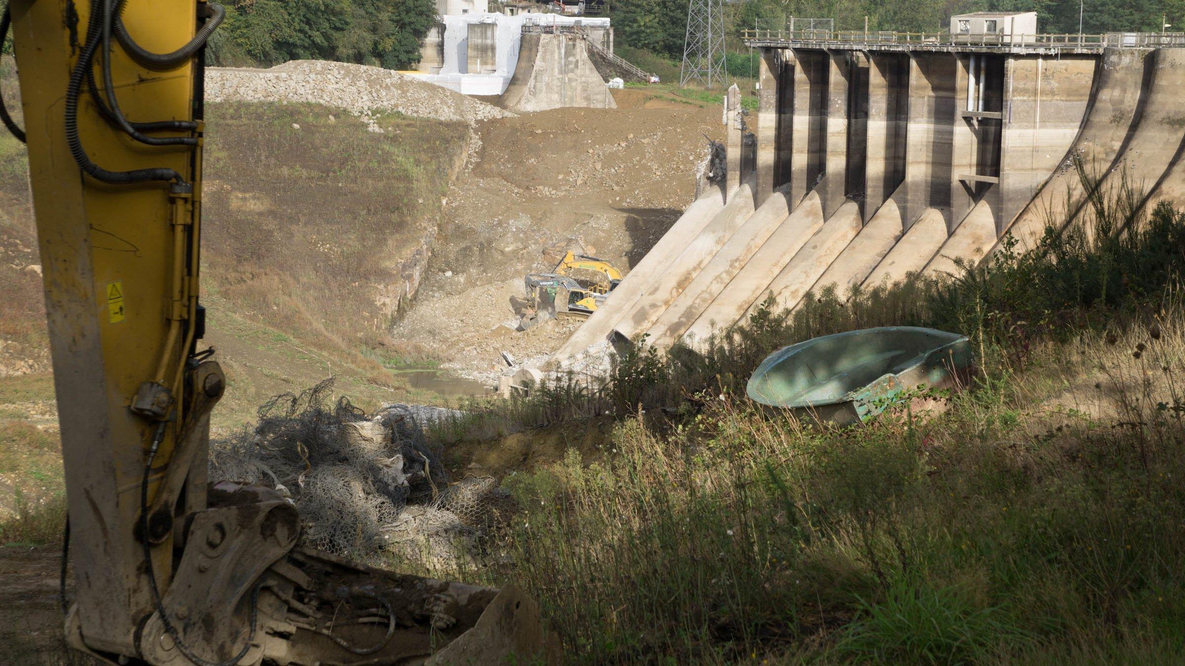Alter Staudamm, teils bereits abgebrochen, mit Bagger