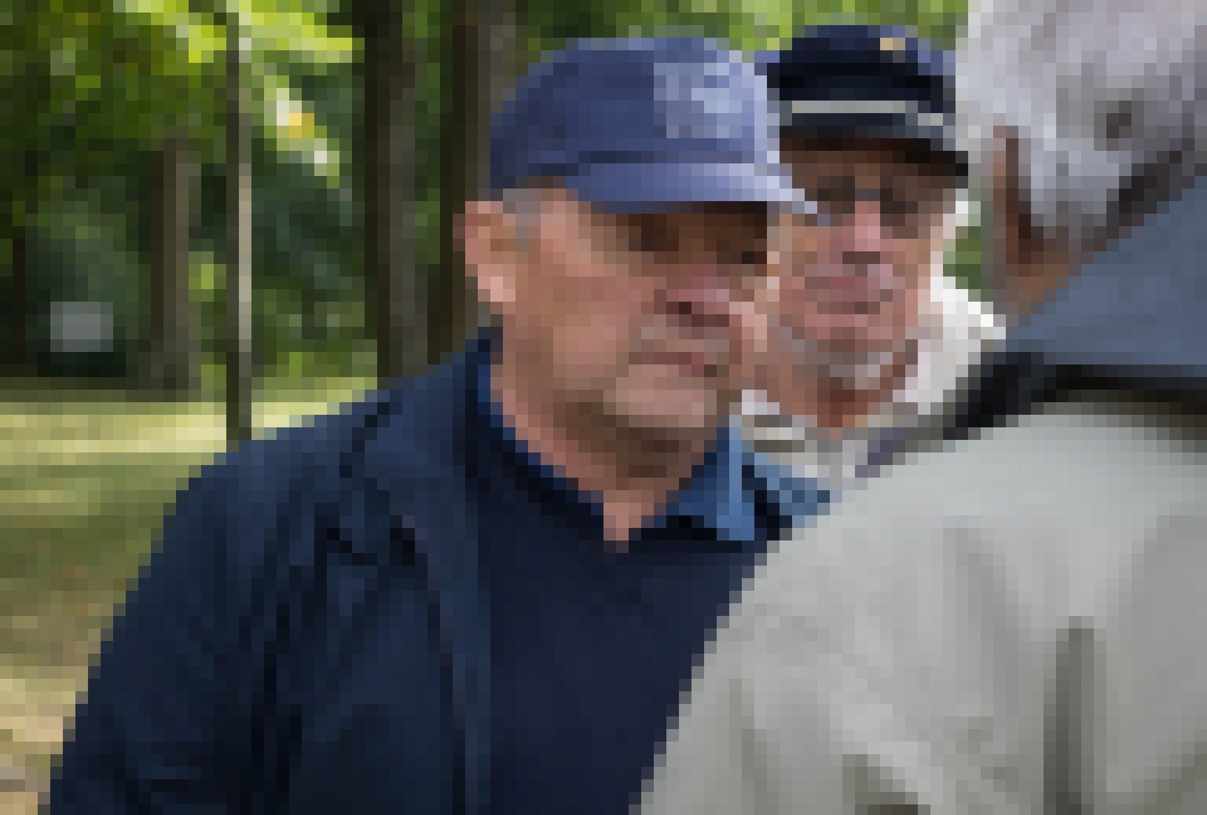 Zwei ältere Männer mit Baseballkappen hören einem dritten Mann zu.