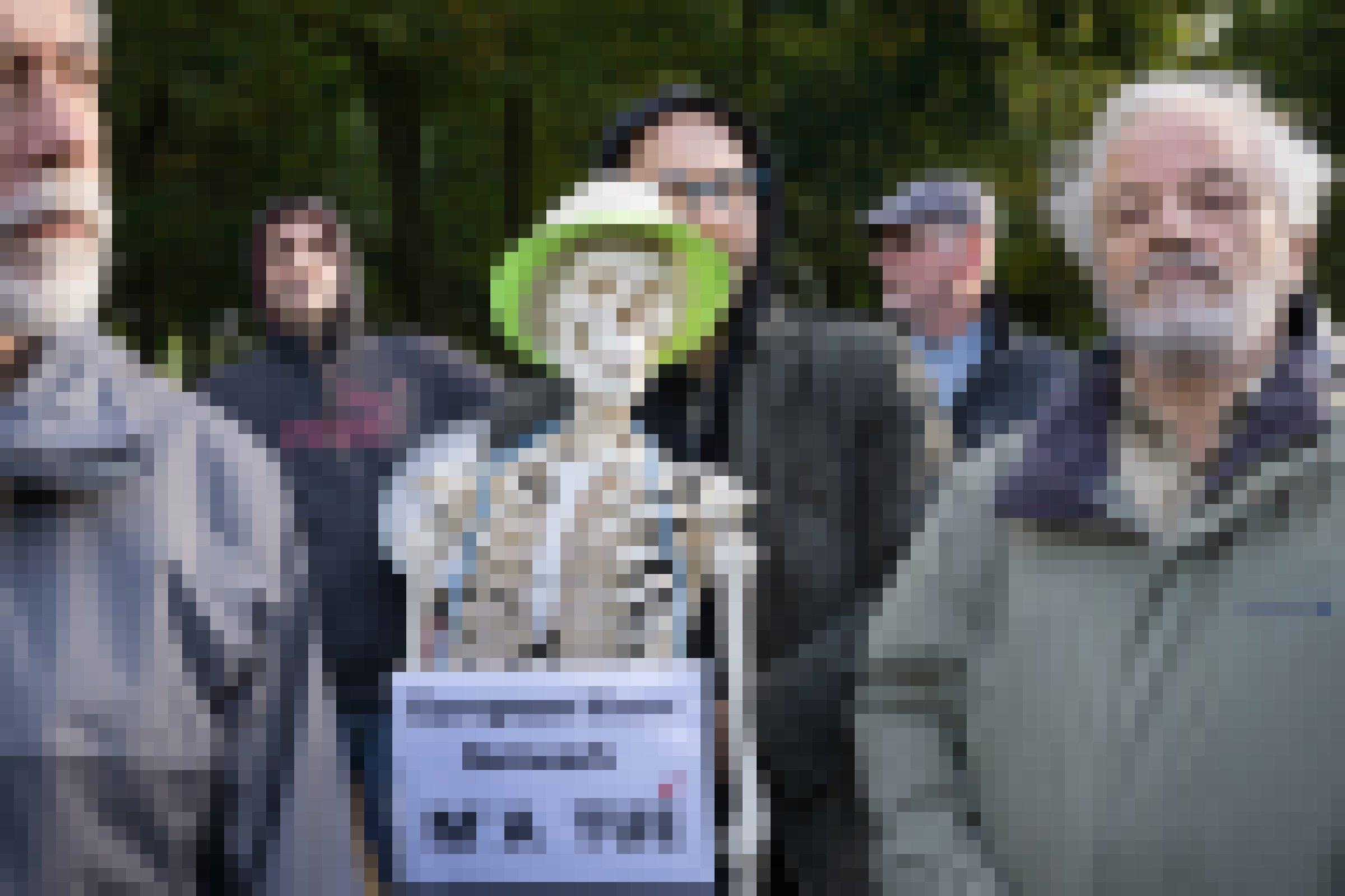 Menschen demonstrieren mit einem Skelett mit grünem Hut.