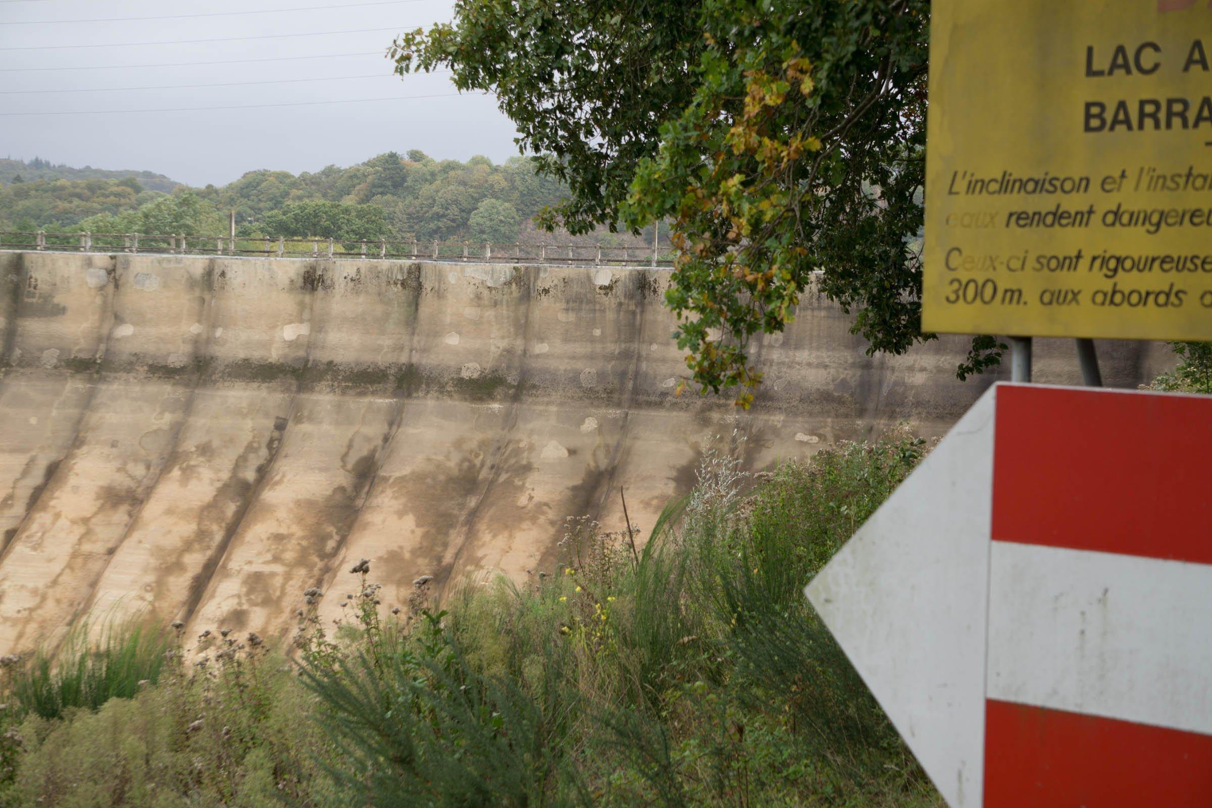 Ein großer alter Staudamm, rechts davon Hinweisschilder.