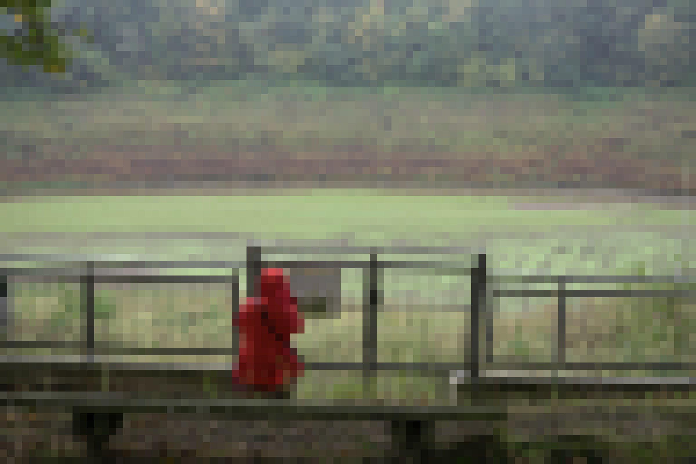 Zaun vor trocken gelegtem Stausee, davor eine Person mit roter Regenjacke