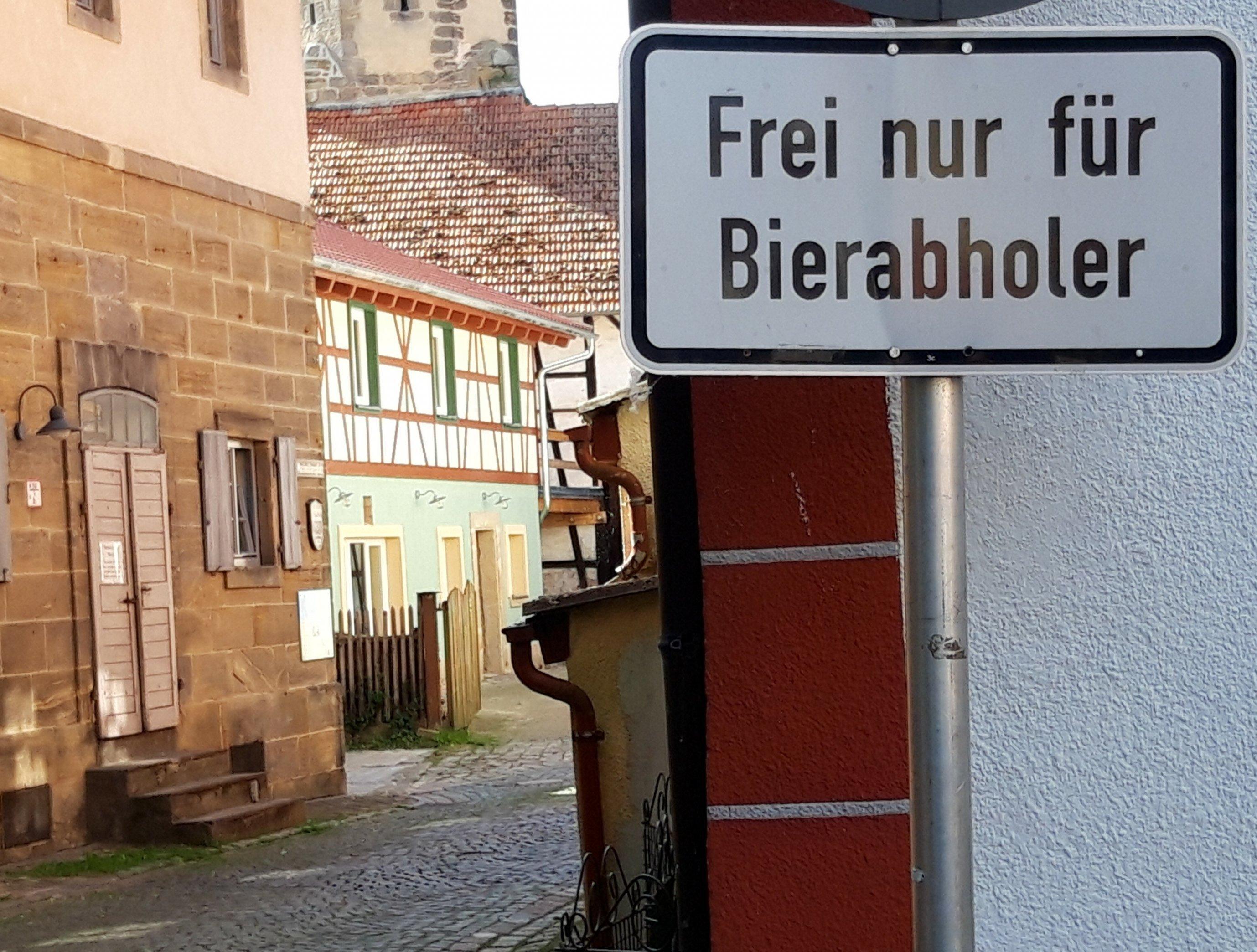"""Vor einer im Abendlicht schimmernden Gasse mit Fachwerkgebäuden über Kopfsteinpflaster steht das Straßenschild mit der Aufschrift """"Frei nur für Bierabholer""""."""