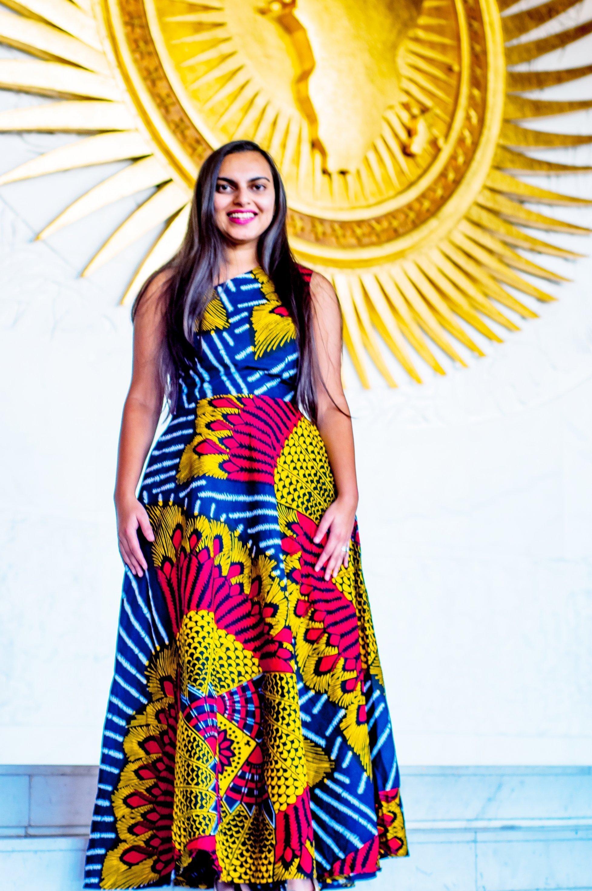 Das Bild zeigt die strahlende Gesundheitsexpertin Shakira Choonara vor dem Emblem der Afrikanischen Union.