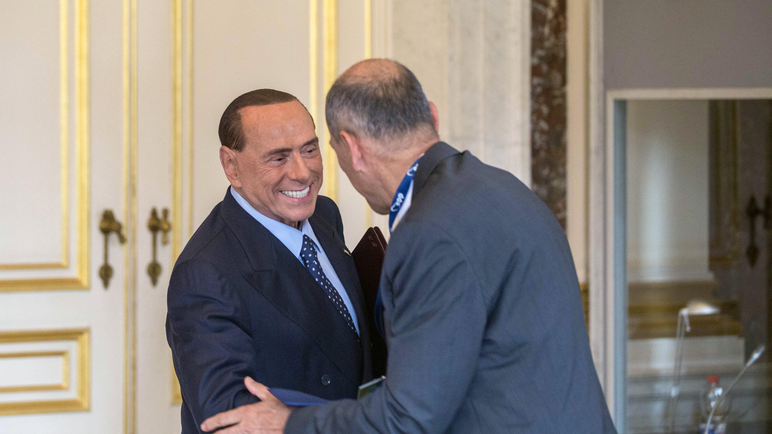 Silvio Berlusconi schüttelt grinsend einem Mann die Hand