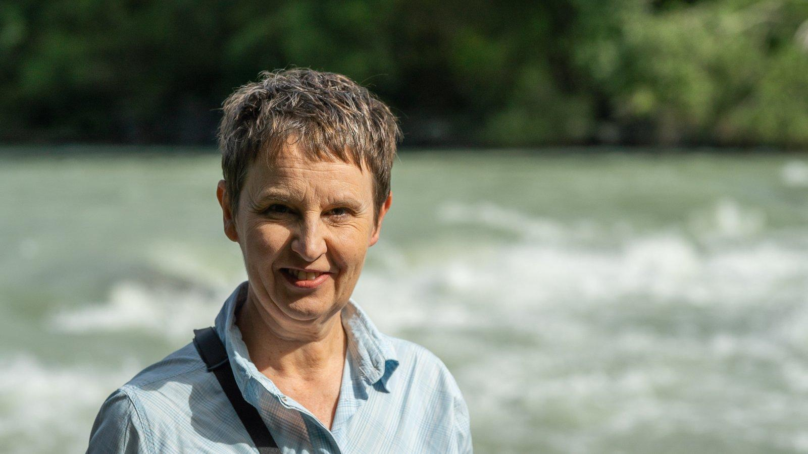 Frau mit kurzen Haaren, im Hintergrund sieht man einen Fluss und Bäume