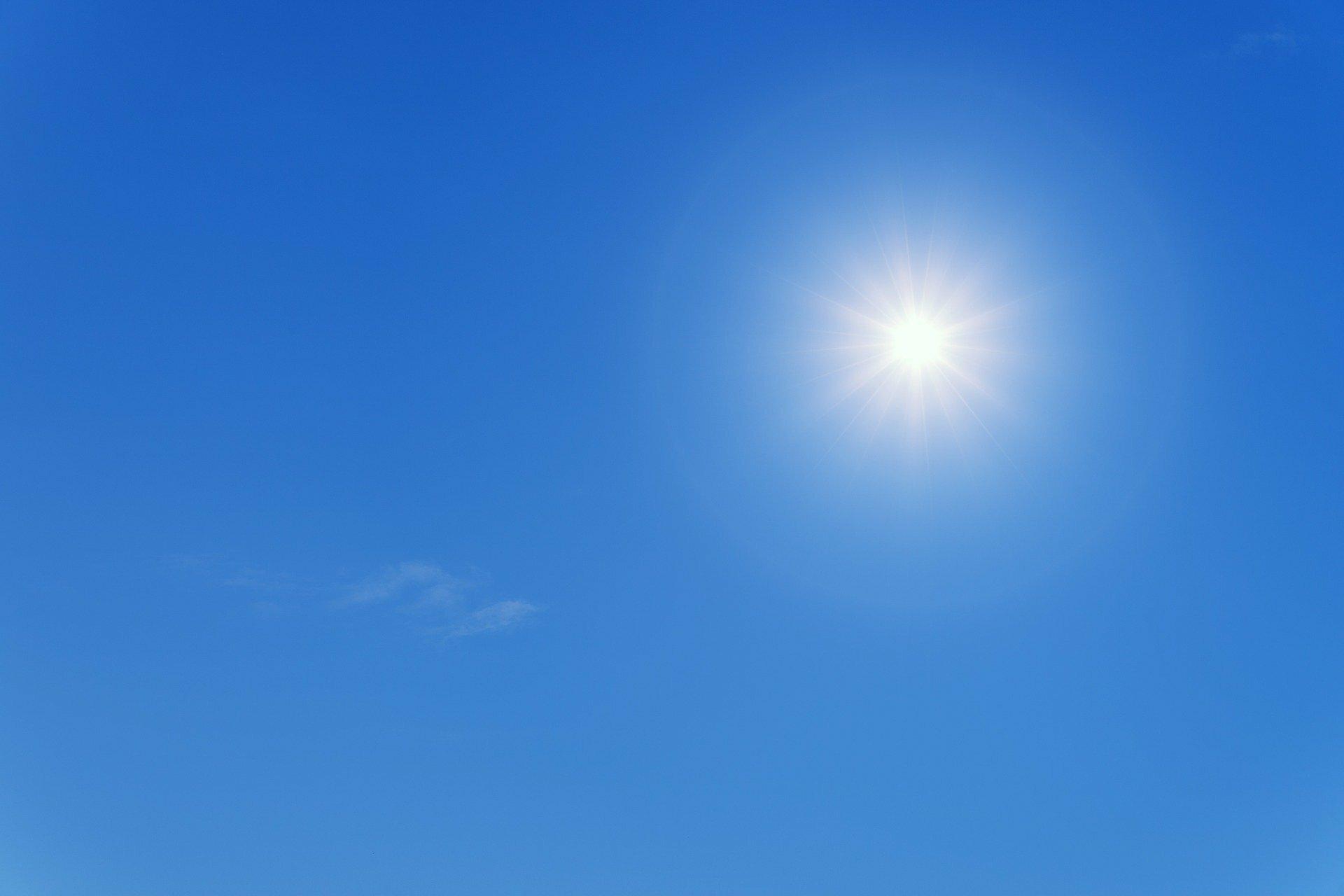 Eine gleißend helle Sommersonne am blauen Himmel.