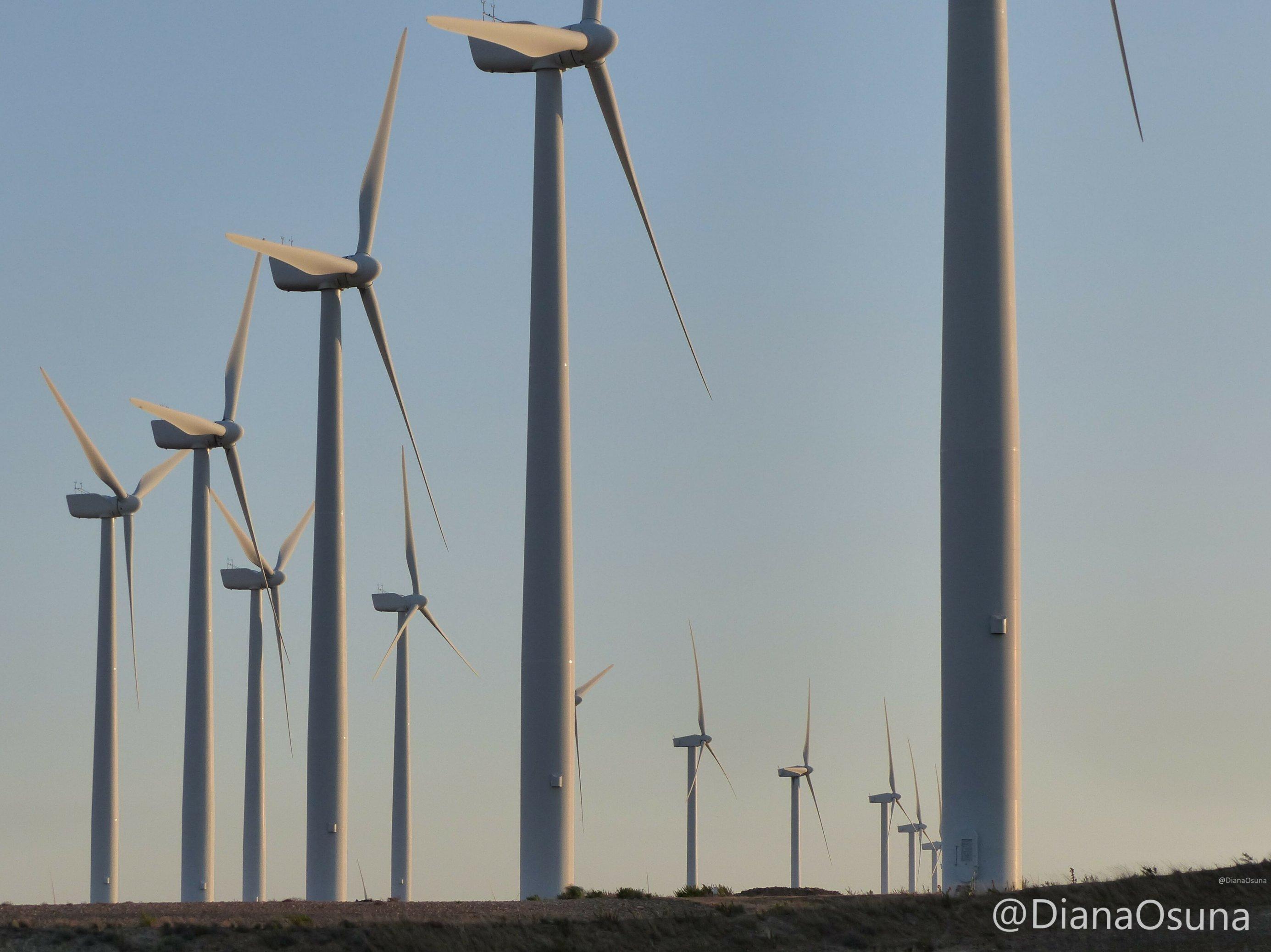 Eine lange Reihe von Windrädern zieht sich über eine Hügelkette