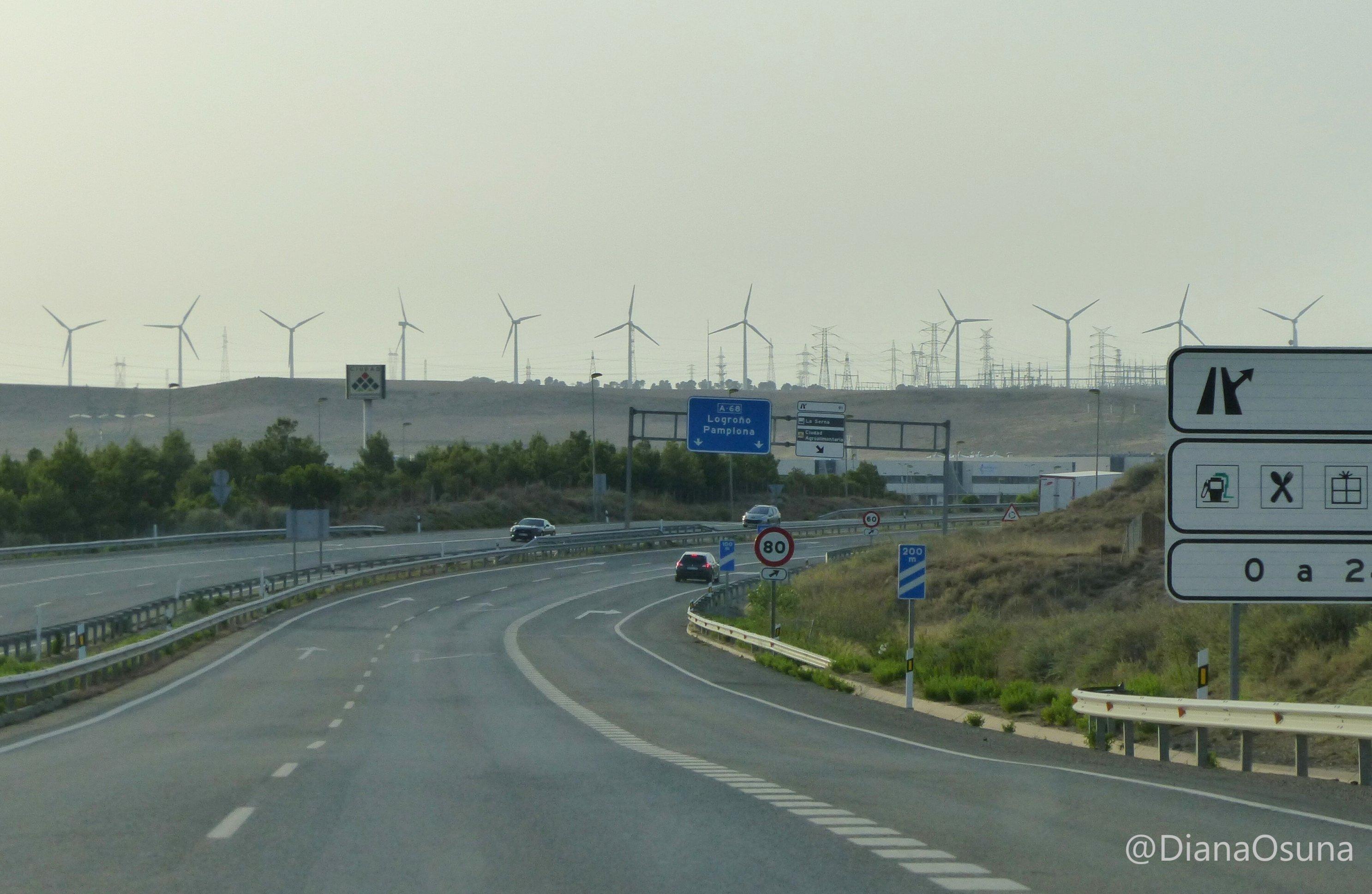 Am Horizont hinter einer Autobahnausfahrt steht eine lange Reihe von Windrädern und Strommasten