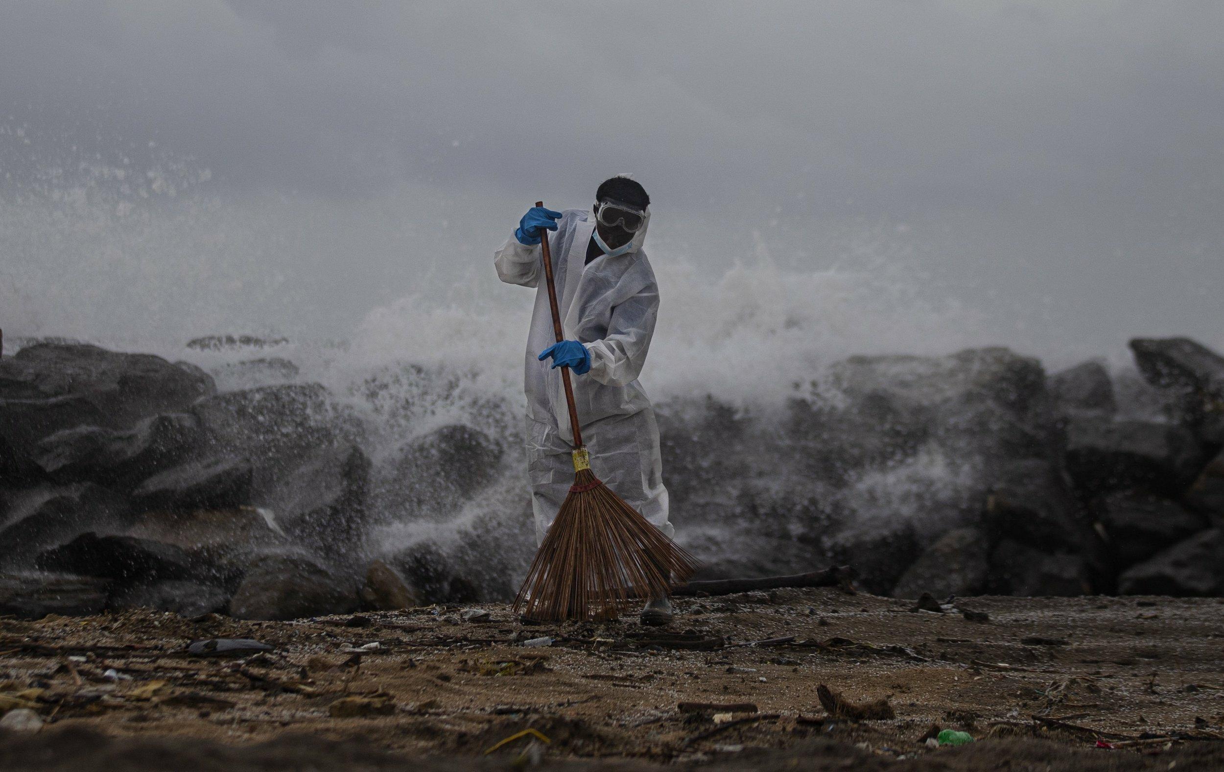 Ein Soldat mit Schutzkleidung fegt vor dem stürmischem Meer mit einem einfachen Rechen kleine weiße Plastikteilchen aus dem Sand.