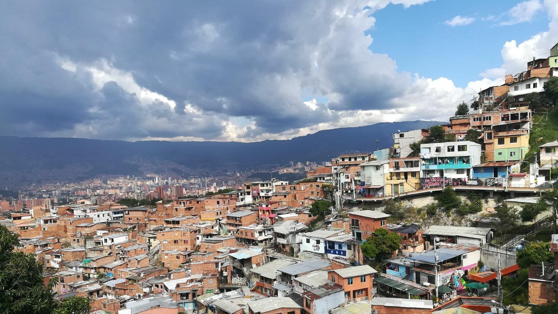 Ein Meer von Häuserdächern an einem steilen Hang. Die meisten Gebäude sind unverputzte Ziegelbauten mit Blechdächern, teilweise bunt angestrichen.