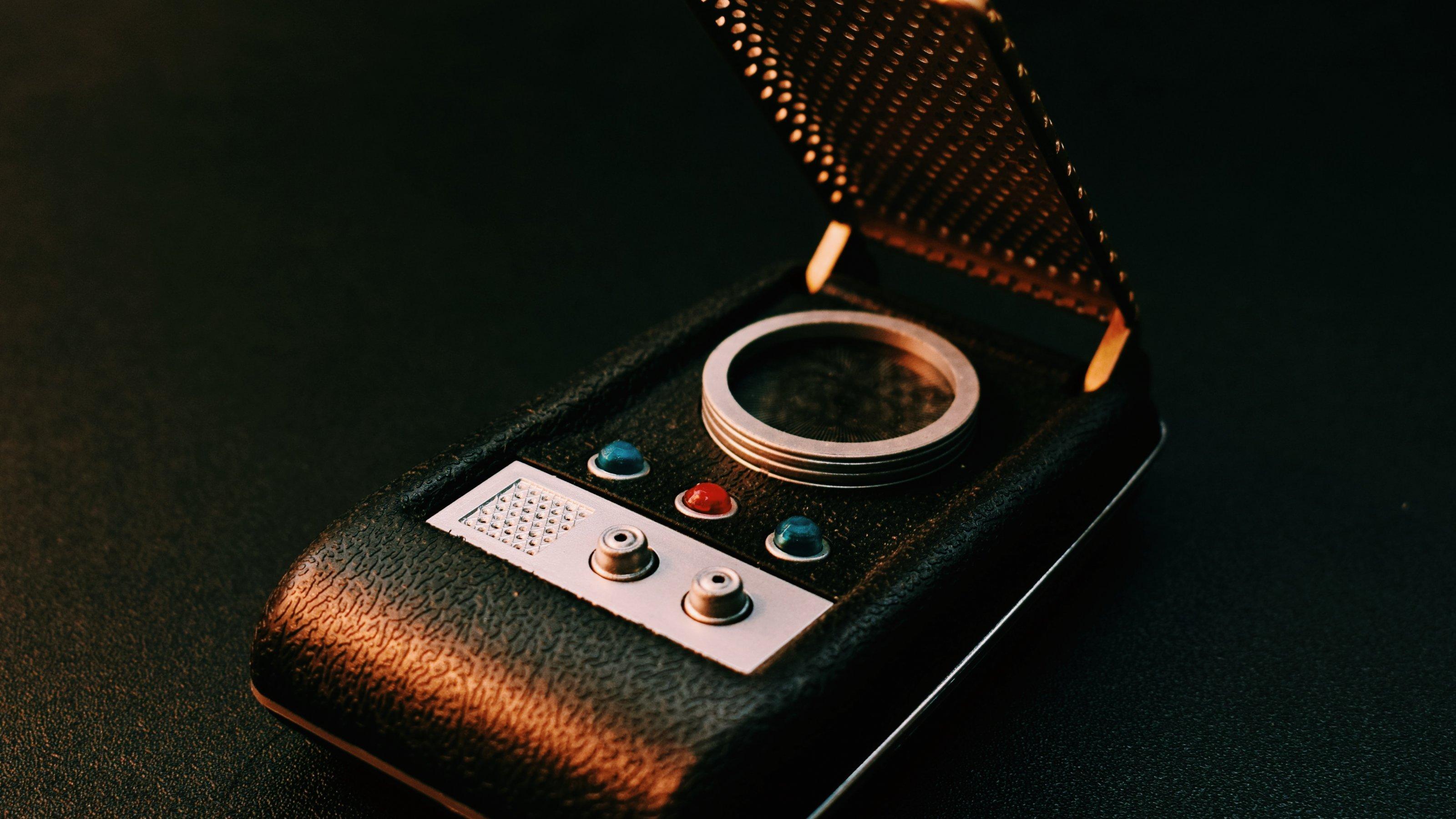Ein Kommunikator aus der Science-Fiction-Serie Star Trek aus den 1960er Jahren. Damals nicht mehr als ein schwarzes Stück Kunststoff mit einer goldenen Gitter-Abdeckung, kleinen Knöpfen und blinkenden Lichtern, so war es doch die Vorlage für das erste Klapphandy von Motorola.