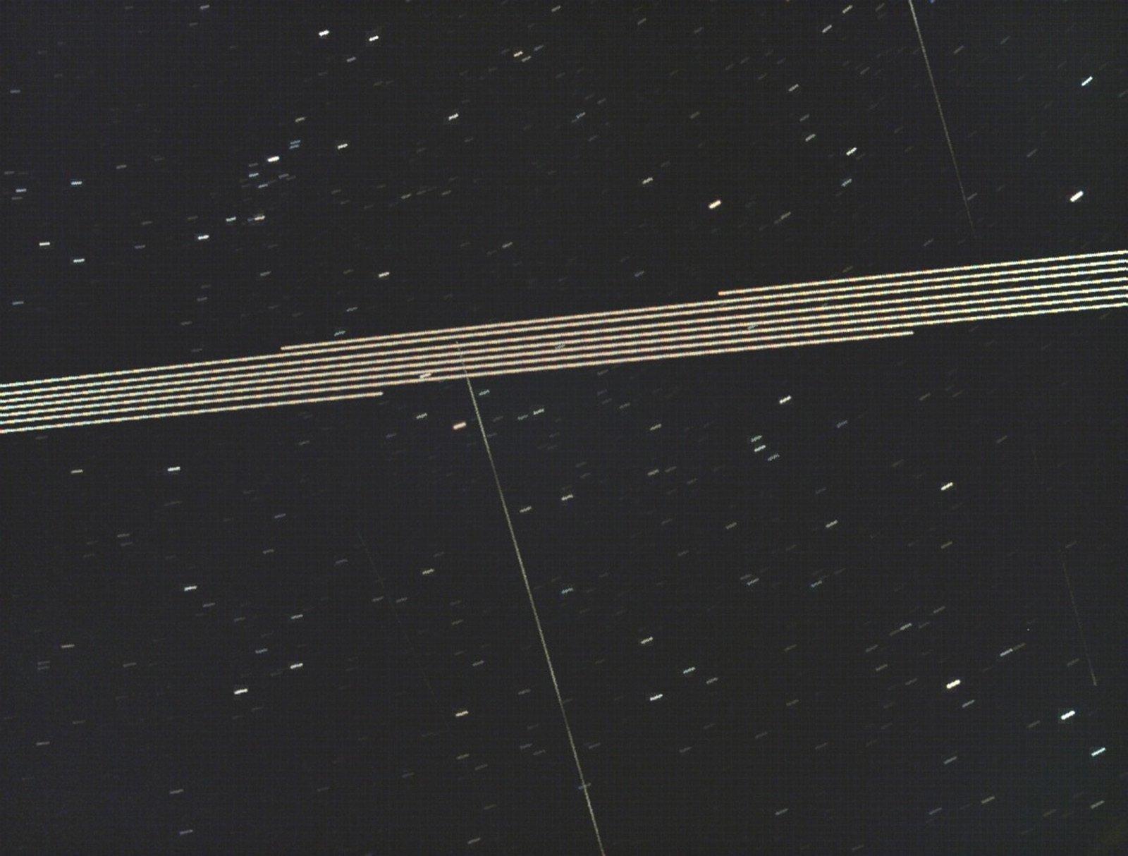 Die Starlink-Satelliten zeichnen sich als helel Spuren vor dem dunklen Himmel ab.