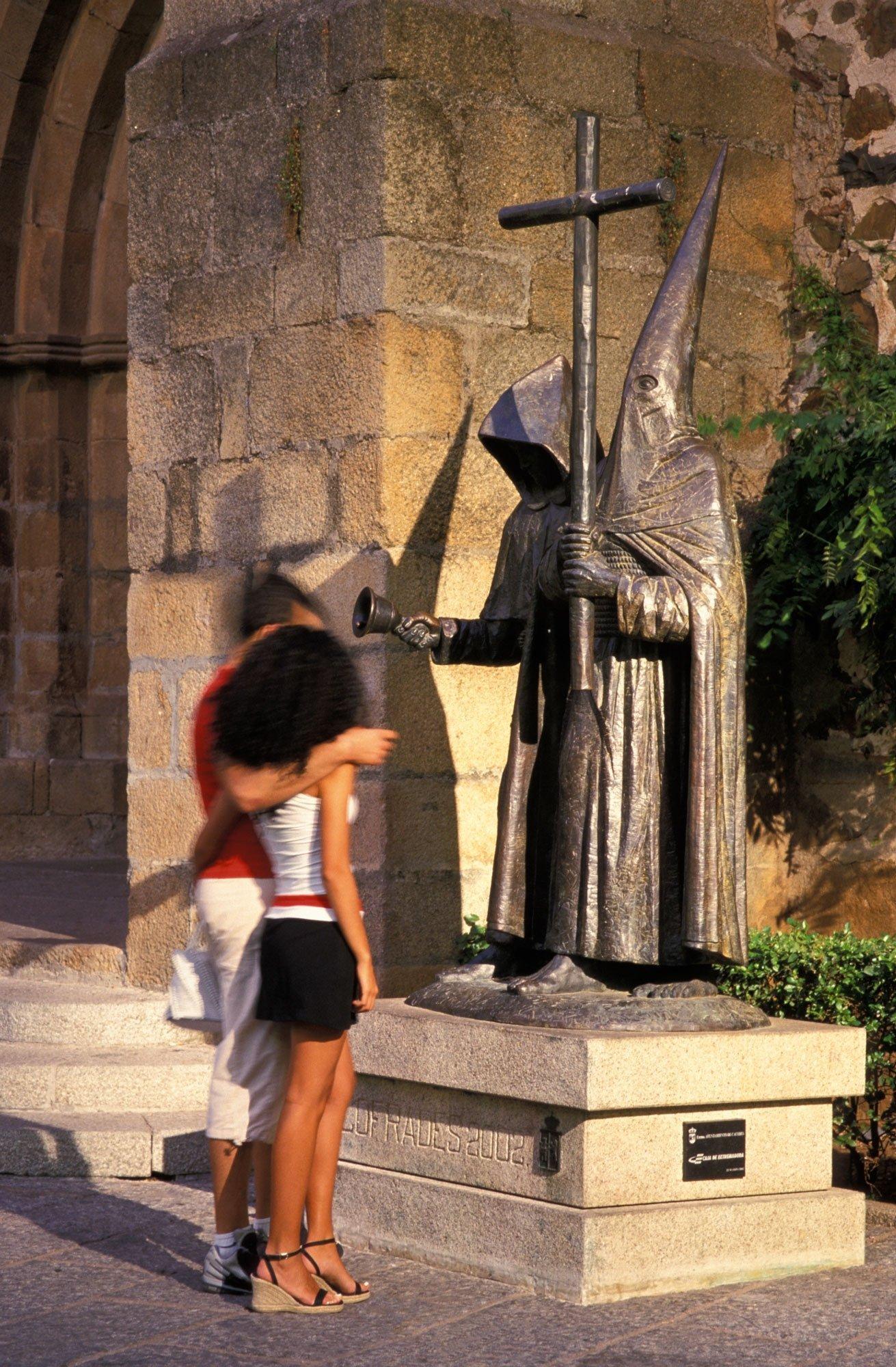 Junges Pärchen vor einer steinernen Statue im südspanischen Caceres. Die Macht der Kirche ist ungebrochen.