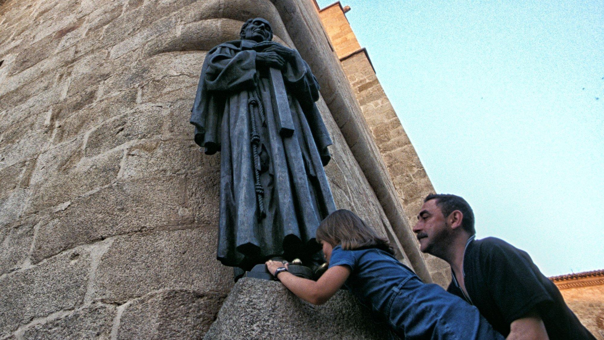 Einer steinernen Statue eines Priesters werden die Füsse geküsst. Eine Tradition im südspanischen Caceres