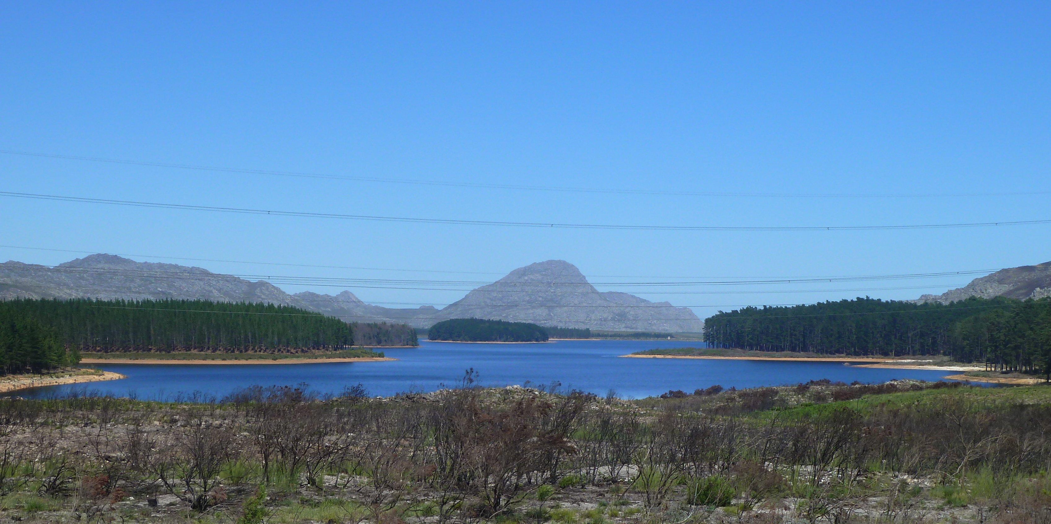 Ein großer Staudamm mit Bäumen an den Ufern und den Bergen Kapstadts im Hintergrund