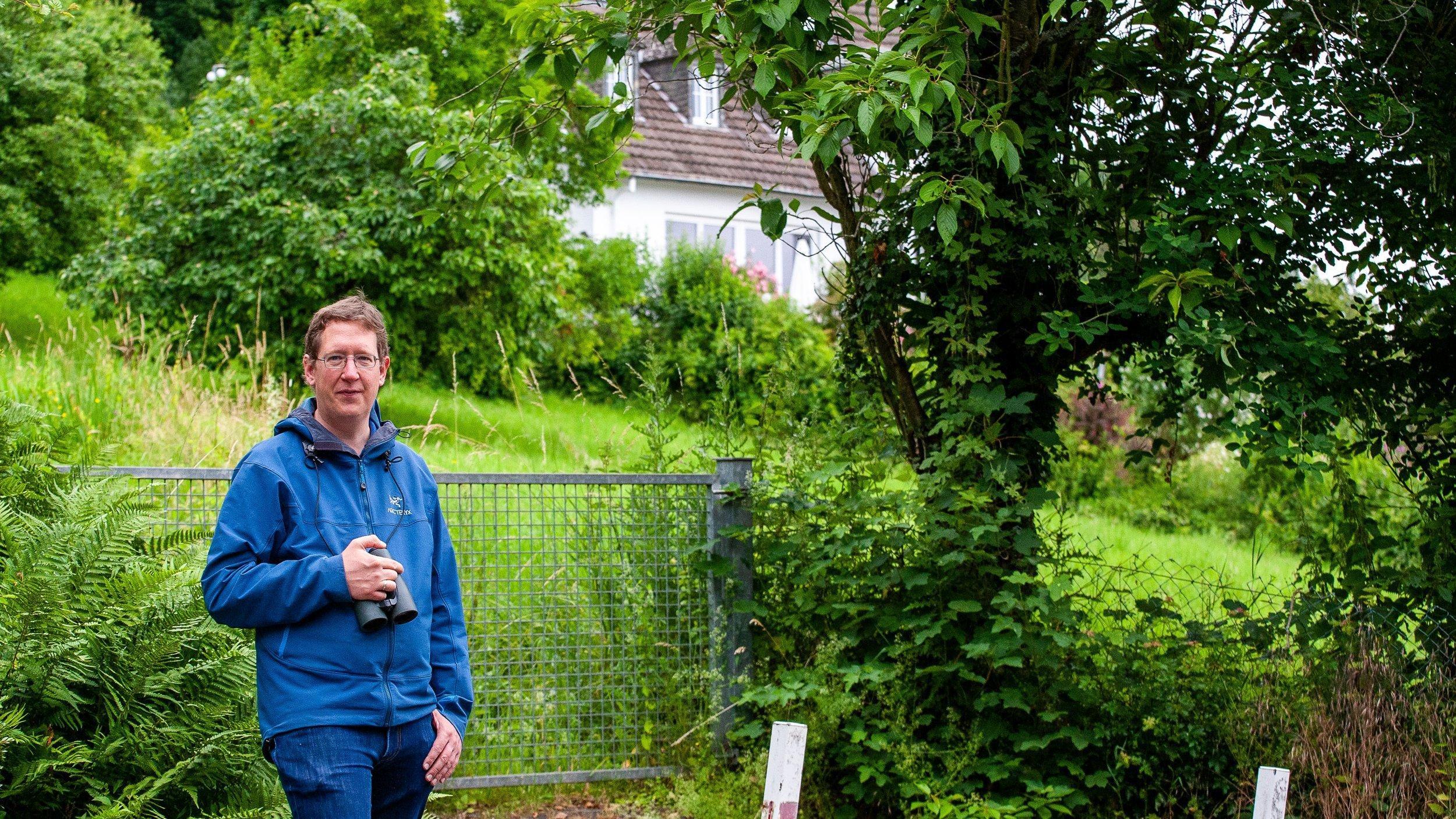Ein Mann mit einem Fernglas um den Hals steht vor einer abschüssigen Wiese mit hohem Gras und ein paar alten Obstbäumen.
