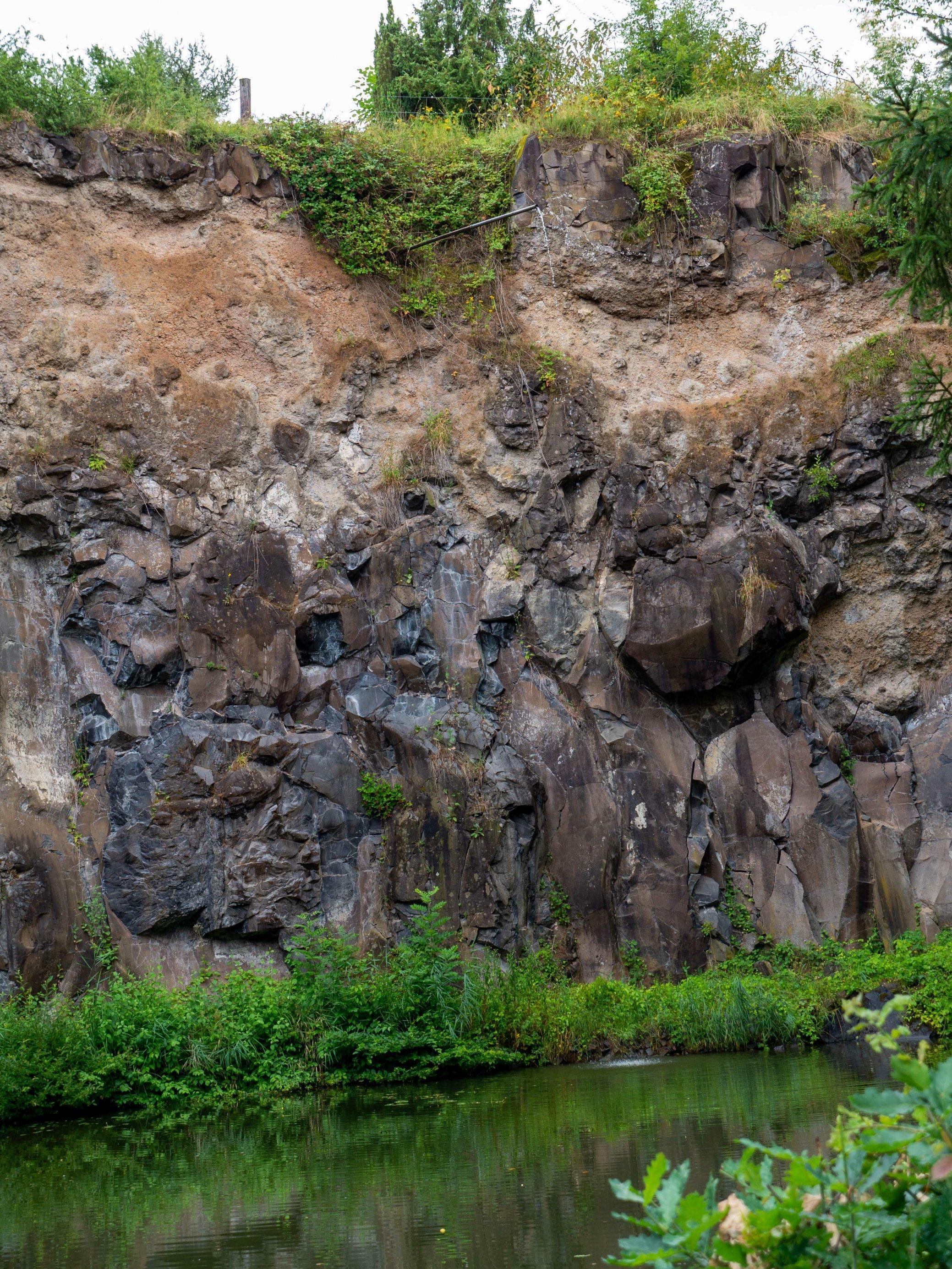 An der Oberkannte eines Steinbruchs ist bewachsener Boden zu erkennen, aus dem Wasser durch ein Rohr abfließt, Darunter Schichten aus beigem Tuff und schwarz-braunen Basaltblöcken. Am Boden des Steinbruchs hat sich ein Teich gebildet, an dessen Ufer grüne Pflanzen sprießen.