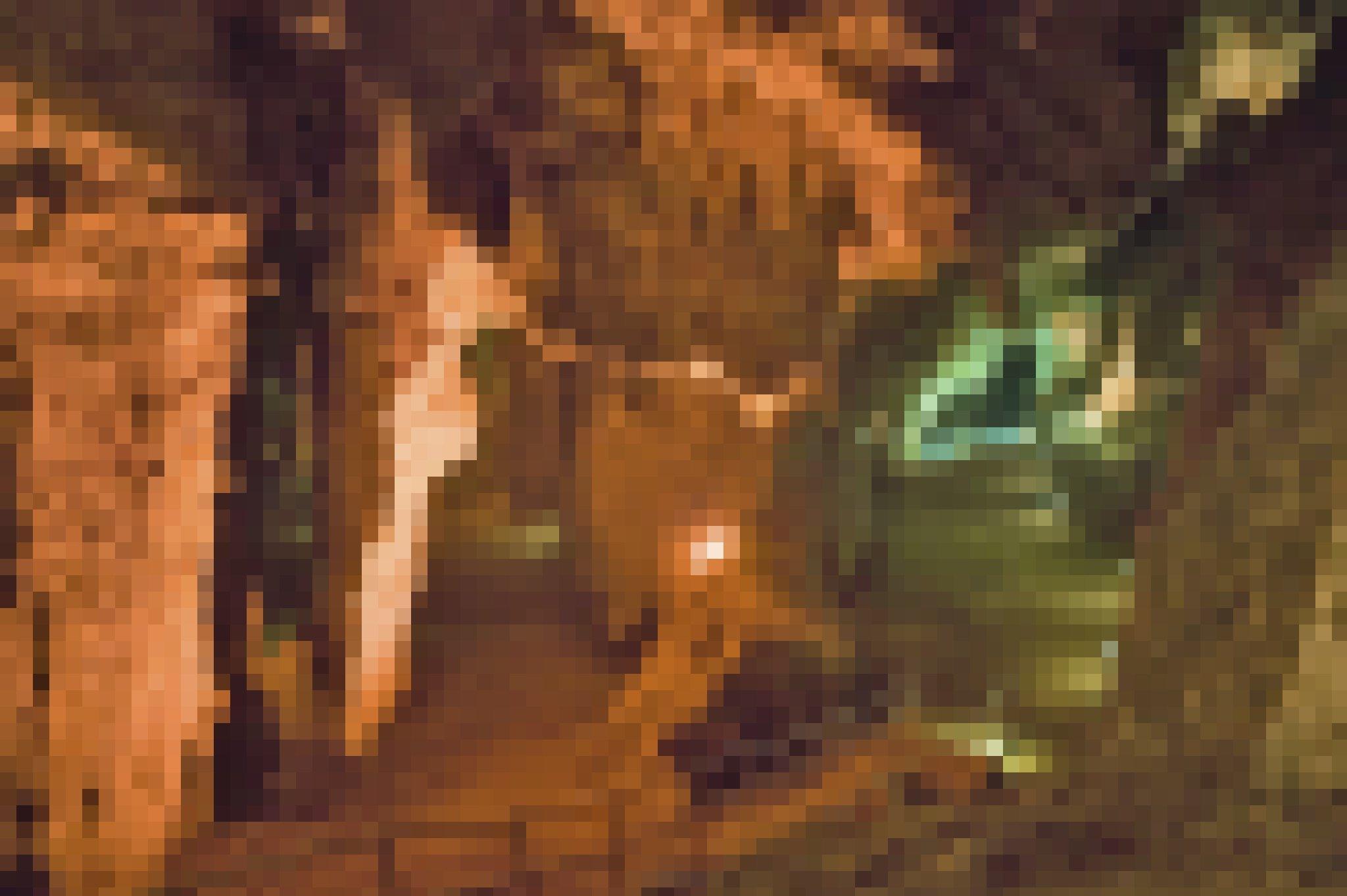 Zu sehen sind links rötlich, rechts grünlich ausgeleuchtete Höhlenwände und –gewölbe, die sich weiter hinten in zwei Gänge verzweigen. Im Vordergrund führt eine Treppe mit Geländer von oben links nach unten rechts in den rechten Gang.
