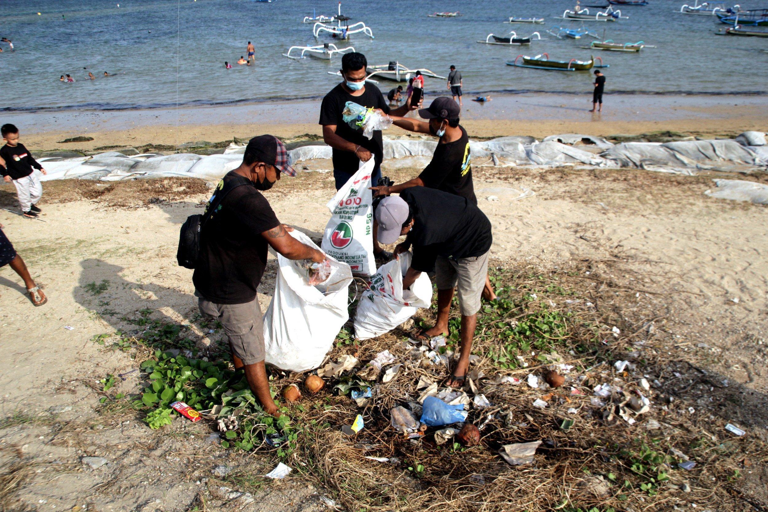 Drei Personen stehen vor dem Meer an einem Strand mit großen weißen Plastiktüten und füllen sie mit Müll, der auf dem Boden liegt.