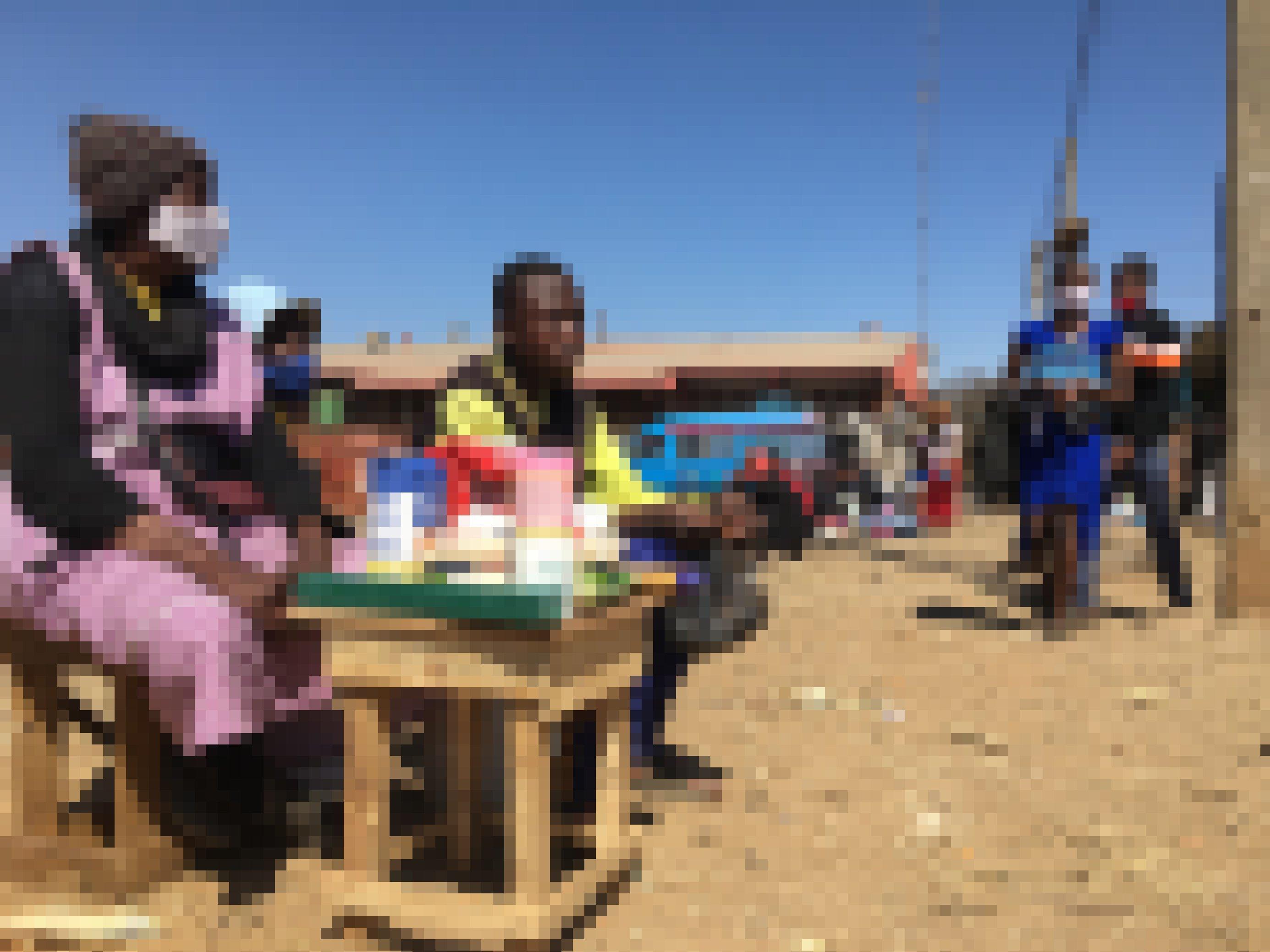 Das Bild zeigt die Straßenhänderlin Vangayi Maisiri, die hinter ihrem kleinen Stand sitzt, auf dem die Waren aufgestellt sind. Im Hintergrund ein paar Passanten.