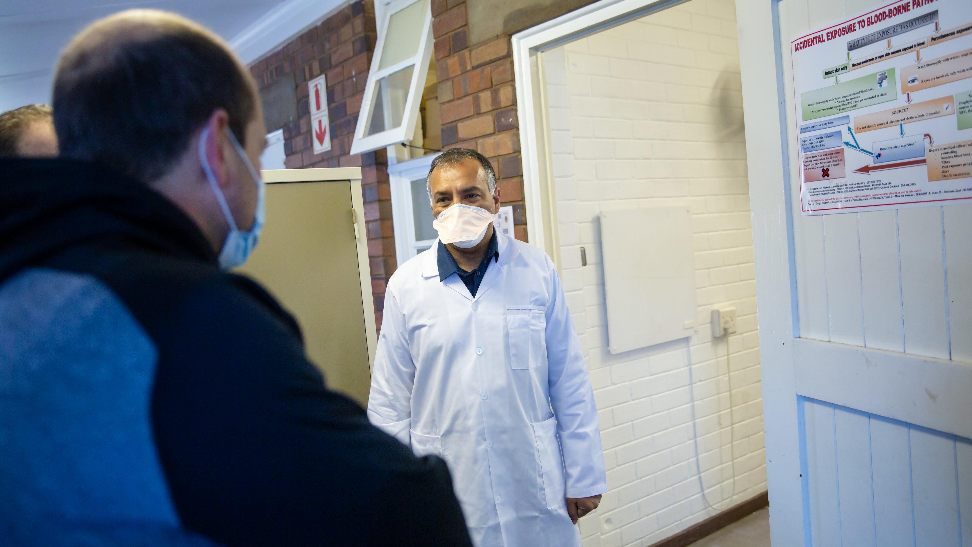 Shabir Madhi, in weißem Kittel mit Mundschutz, begrüßt einen Teilnehmer der Impfstudie in Johannesburg
