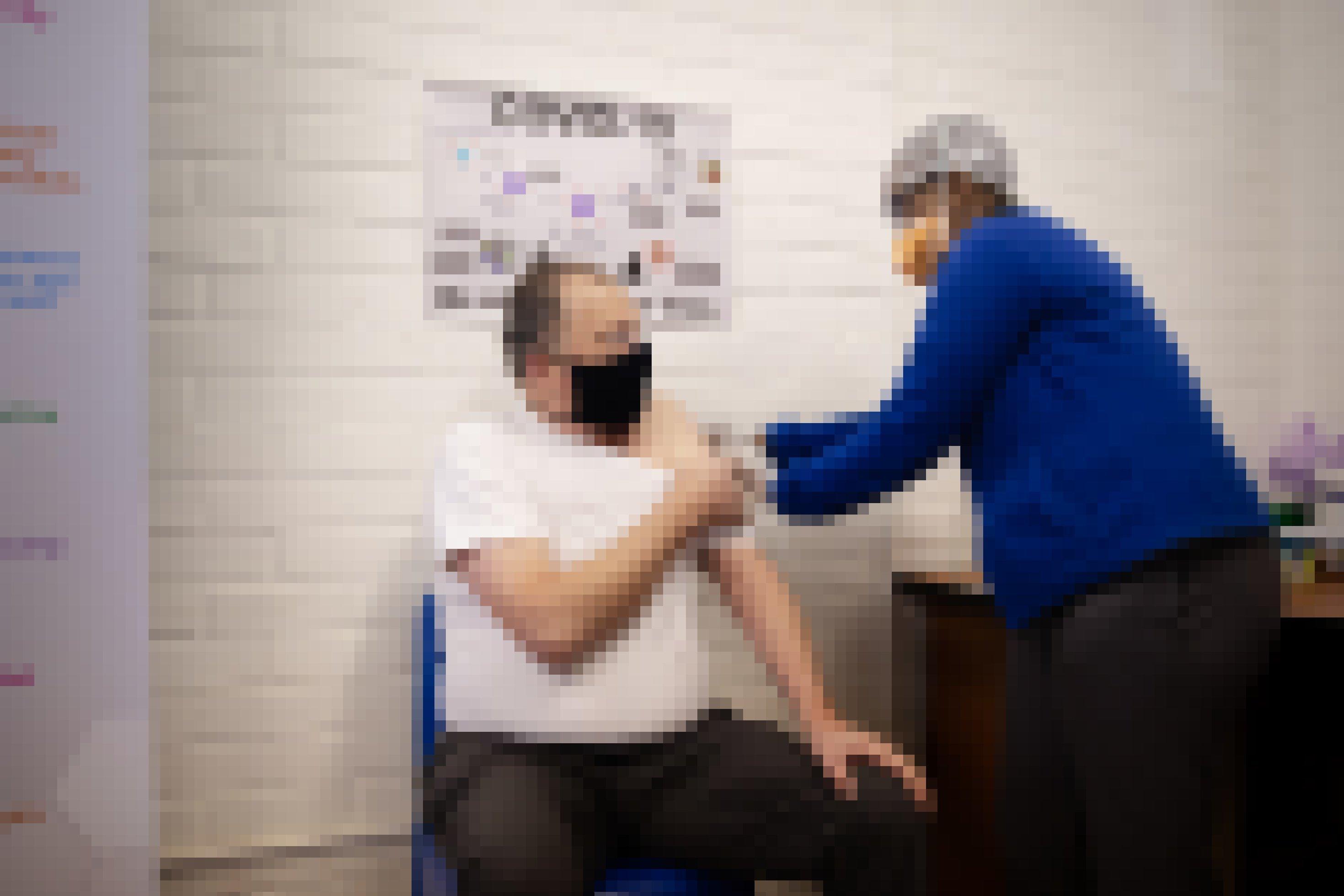 Professor Martin Veller bekommt die Injektion mit der Impfung bzw dem Placebo, er trägt eine Maske, ebenso wie der Mitarbeiter, der ihm die Spritze gibt.