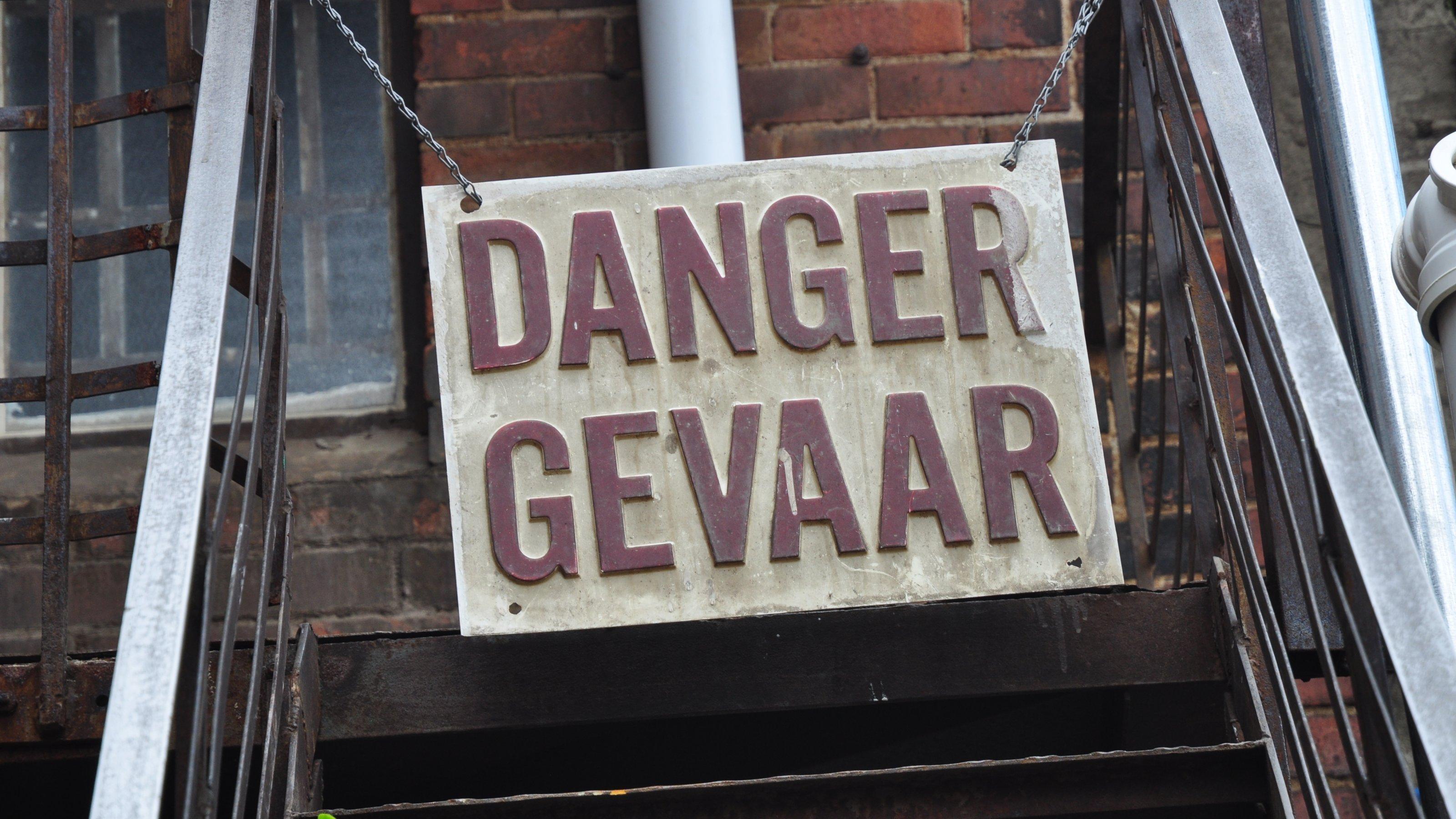 Das Foto zeigt ein Schild, das einen Treppenaufgang versperrt, mit der Aufschrift: Danger. Gefahr.