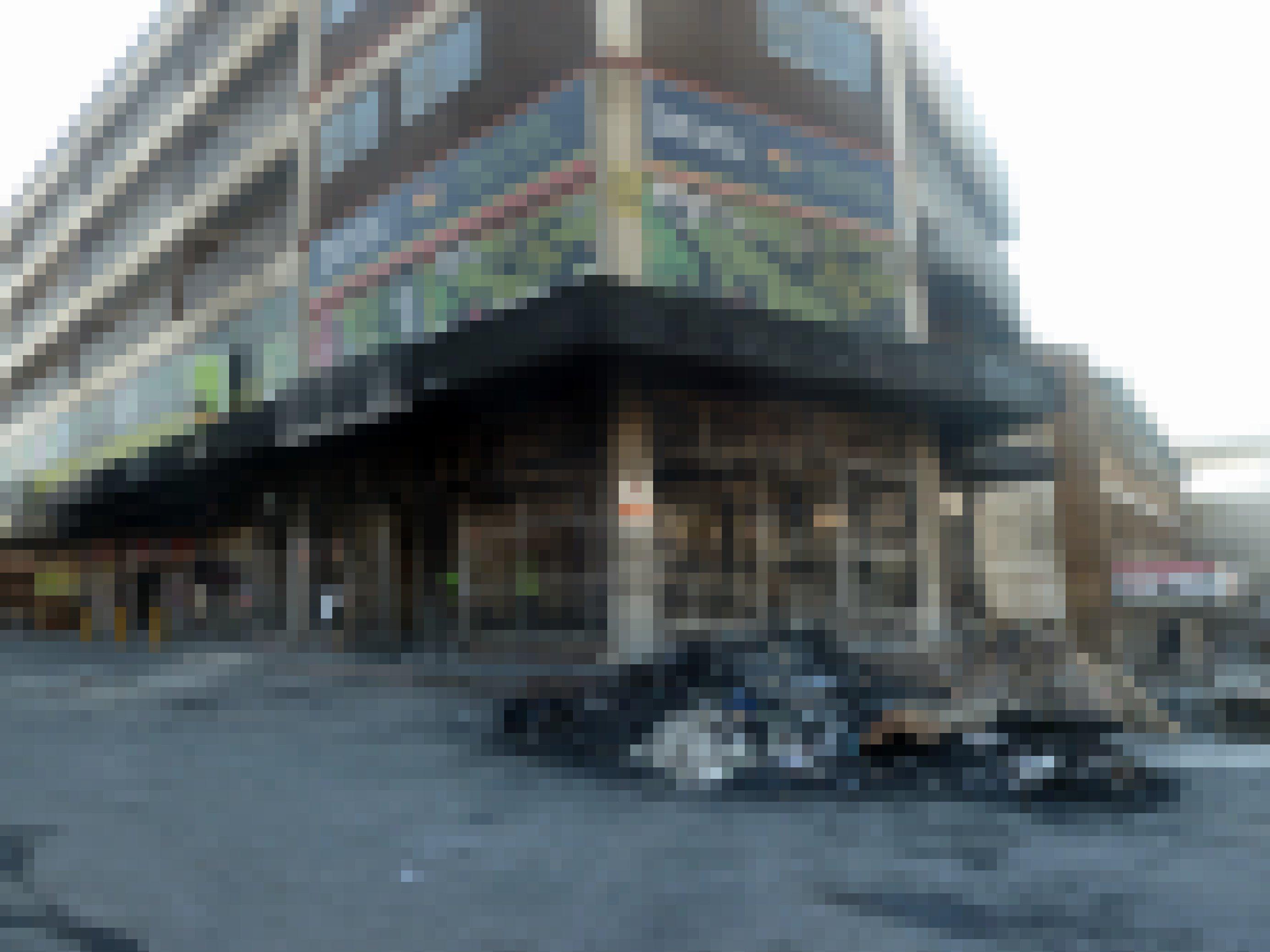Ein ausgebrannter Laden an einer Straßenecke. Die Fenster sind zersprungen. Davor liegt ein Haufen Schutt.
