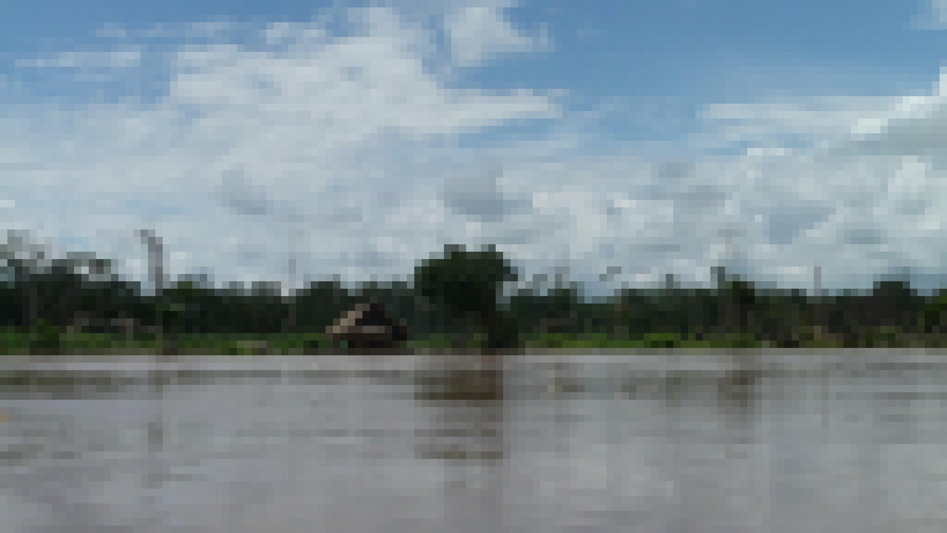 Der Paranapura-Fluss bei Hochwasser. Am Ufer sieht man ein palmstrohbedecktes Holzhaus und über der grünen Wand des tropischen Regenwaldes türmen sich Regenwolken.