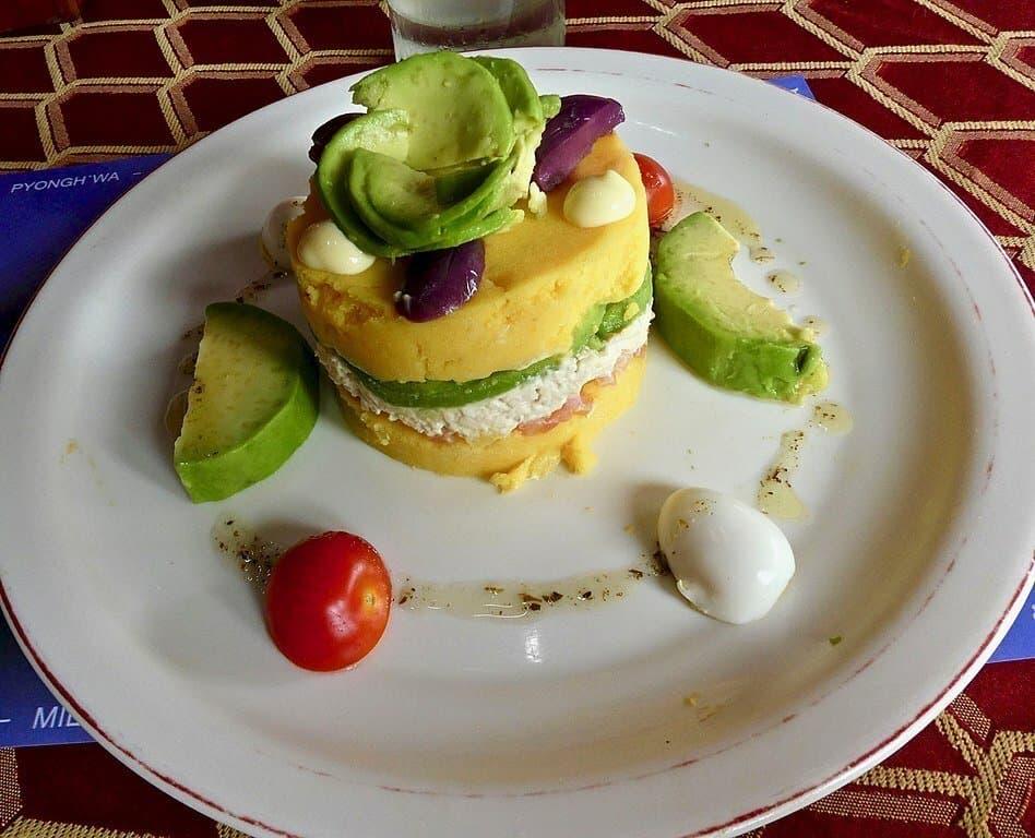 Weißer runder Teller auf einem Tisch. Darauf ein rundes Törtchen, unten gelb, dazwischen eine Schicht mit Mayonnaise und Avocado, darüber wieder gelbe Paste. Dekoriert mit einem Salatblatt, einer Olive und kleinen Stückchen gekochten Eis.