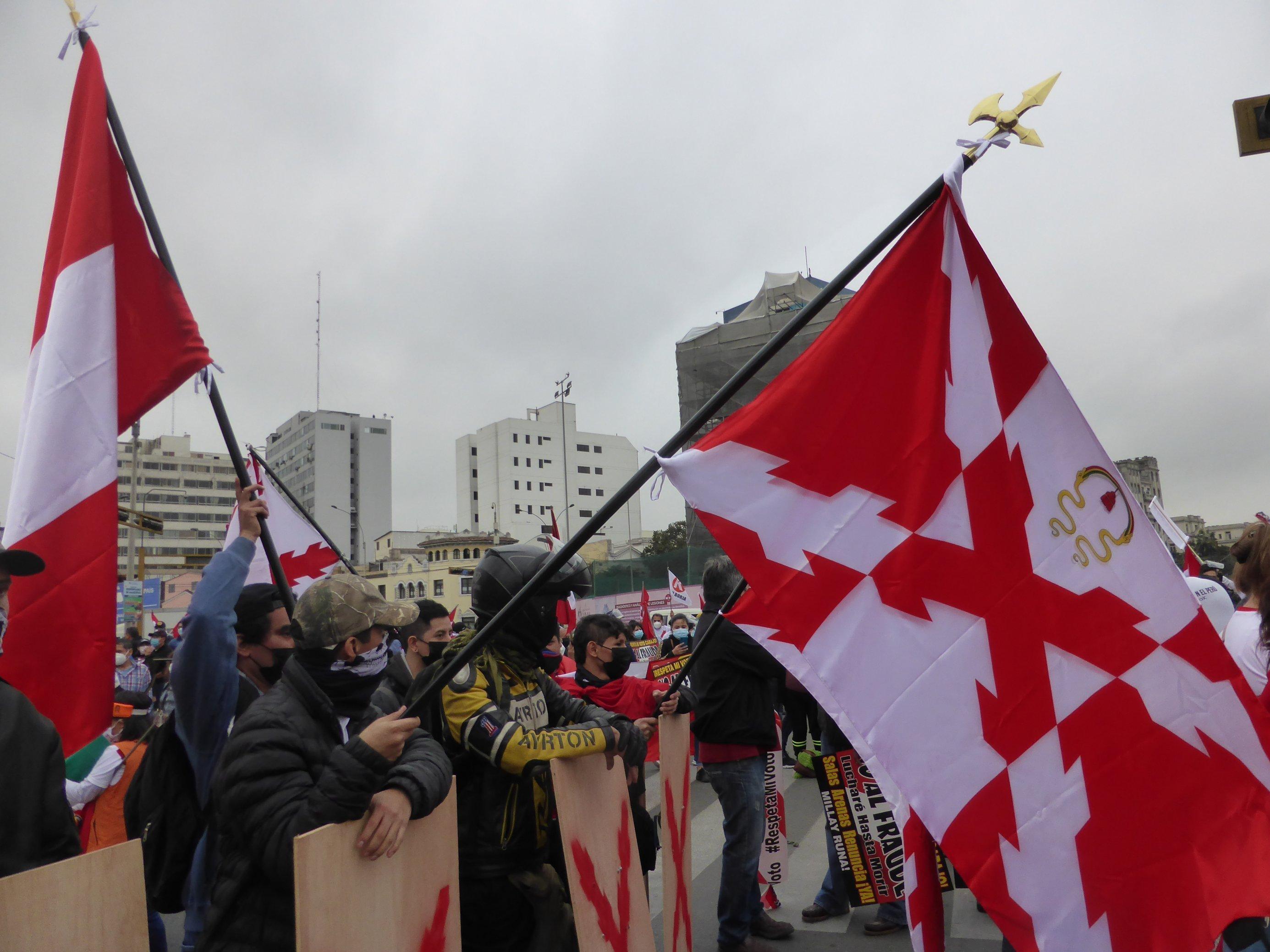Demonstranten mit Fahnen, die ein quer gelegtes rotes Kreuz zeigen.