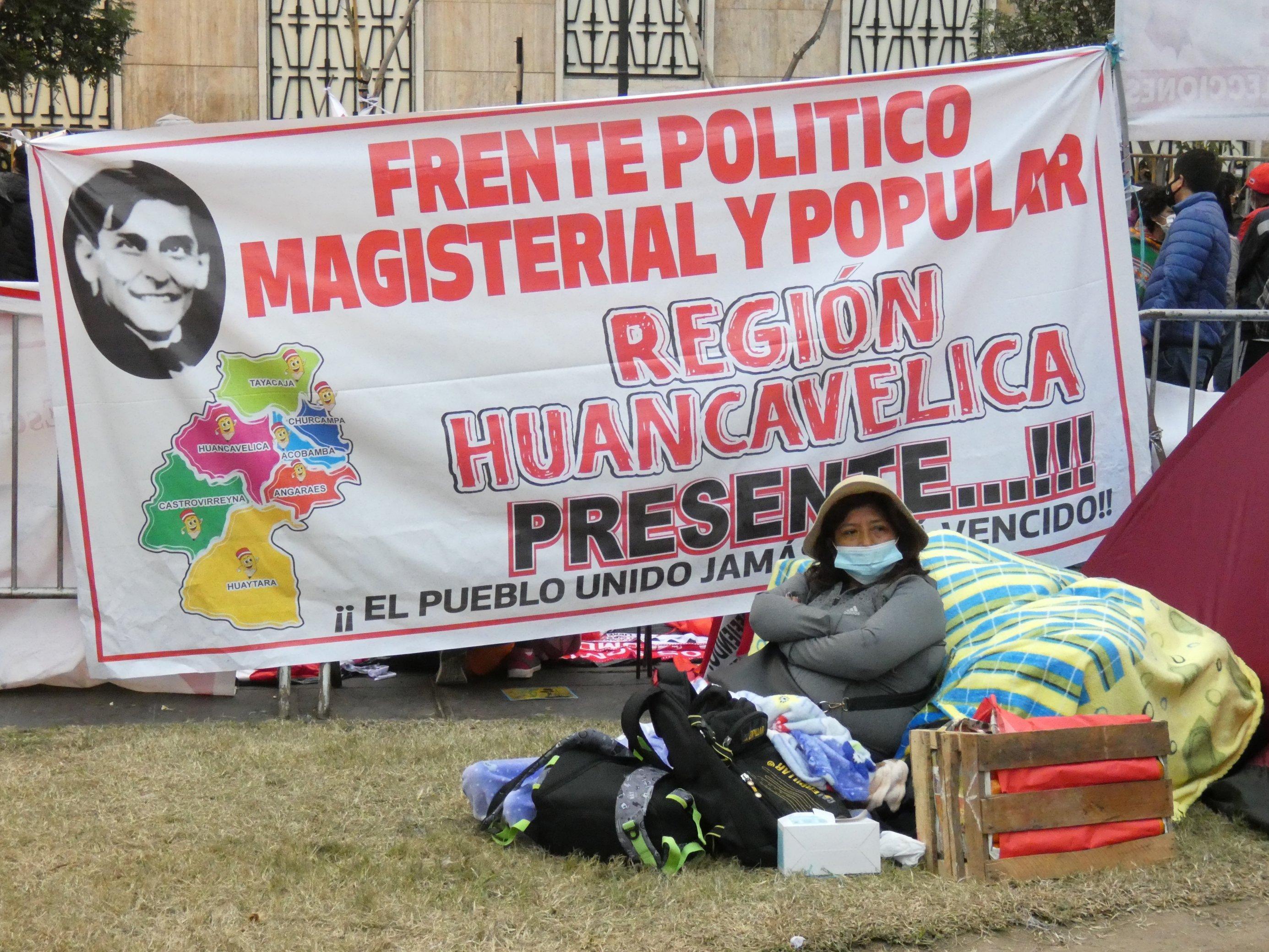 Ein großes Plakat mit der spanischen Aufschrift der Lehrergewerkschaft; davor sitzt eine Person mit viel Gepäck auf dem Rasen.