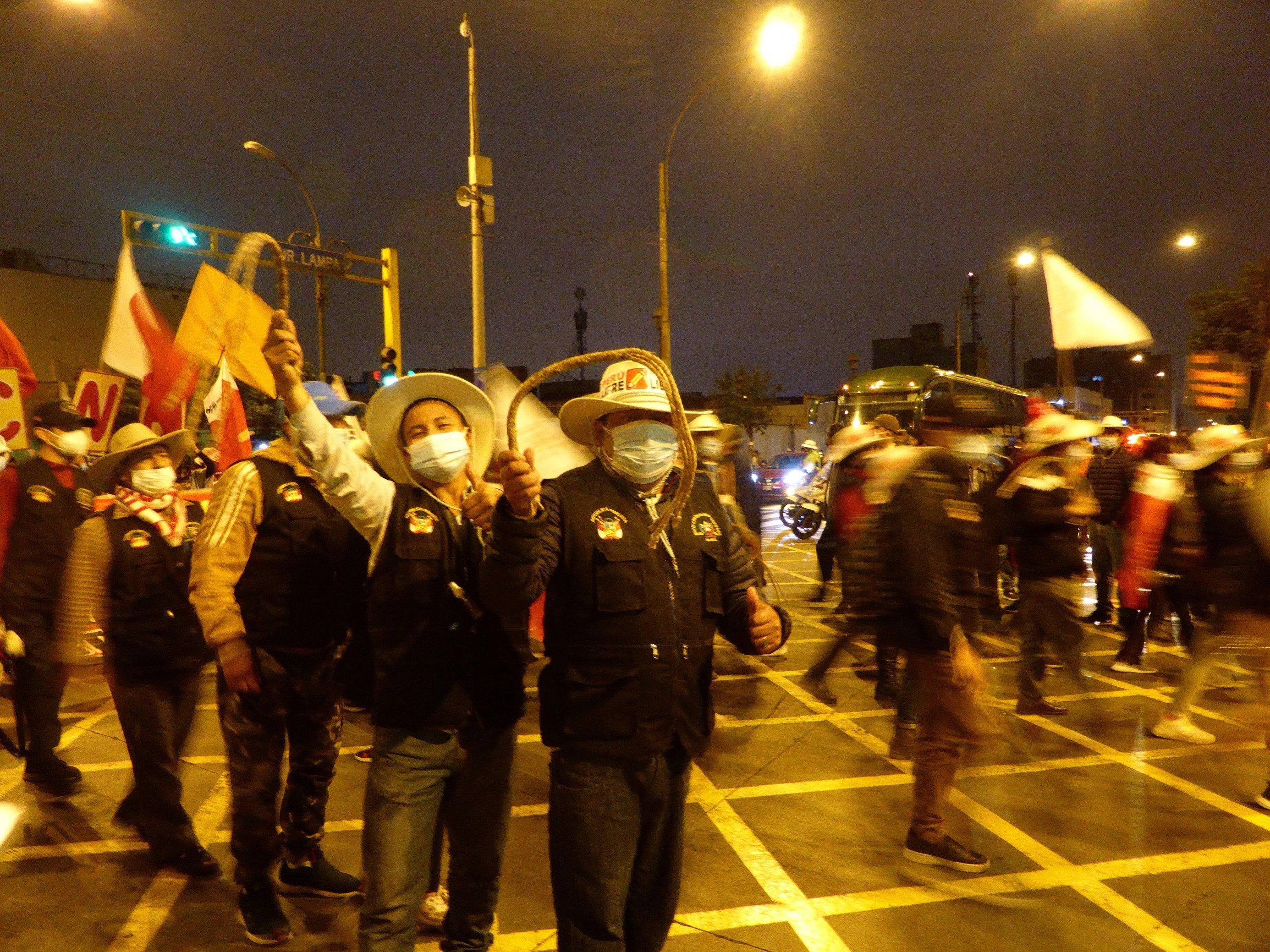 Nachts auf einem Platz in Lima. Zwei Männer inmitten mehrerer Menschen, mit Strohhüten, Mundschutz, schwingen zwei kleine Hanfgeißeln.
