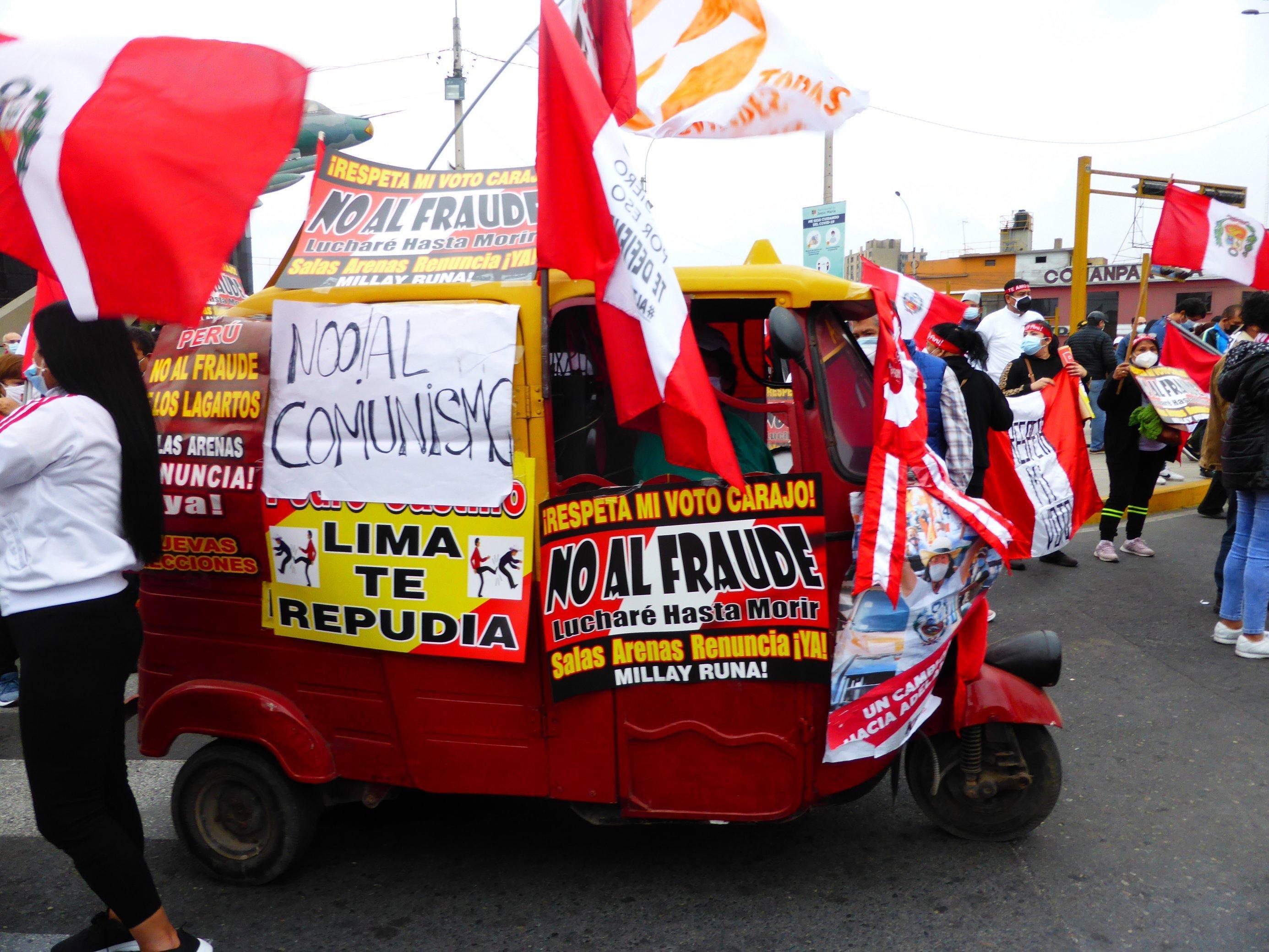 Eine dreirädrige Autorikscha mitten in einer Demo. Personen, die rot-weiße Fahnen schwingen, die Landesfarben Perus.