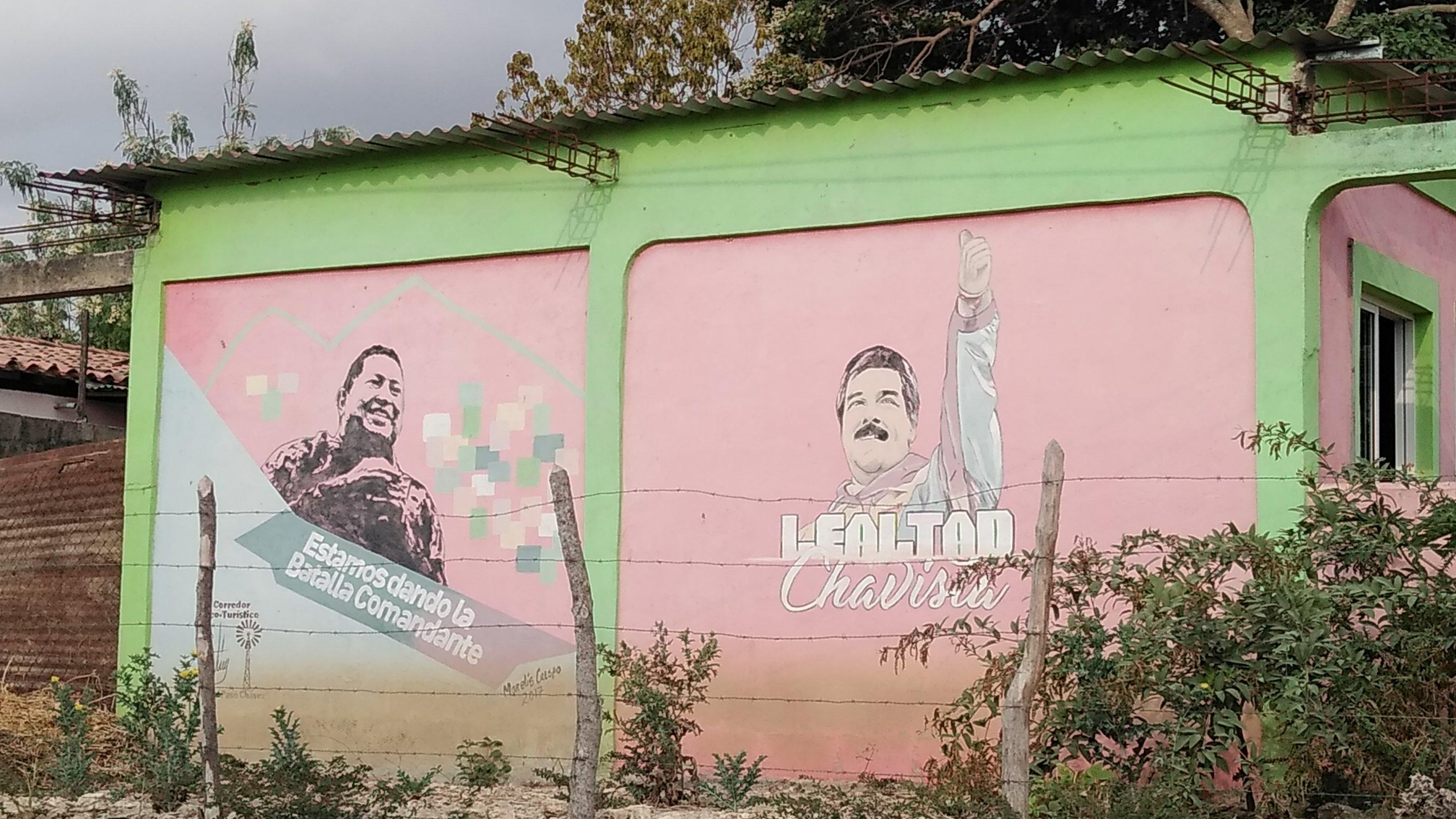 Hellgrüne Häuserwand, auf der zwei gemalte Figuren zu erkennen sind: links der verstorbene venezolanische Präsident Hugo Chavez, rechts der jetzige Präsident Nicolas Maduro.