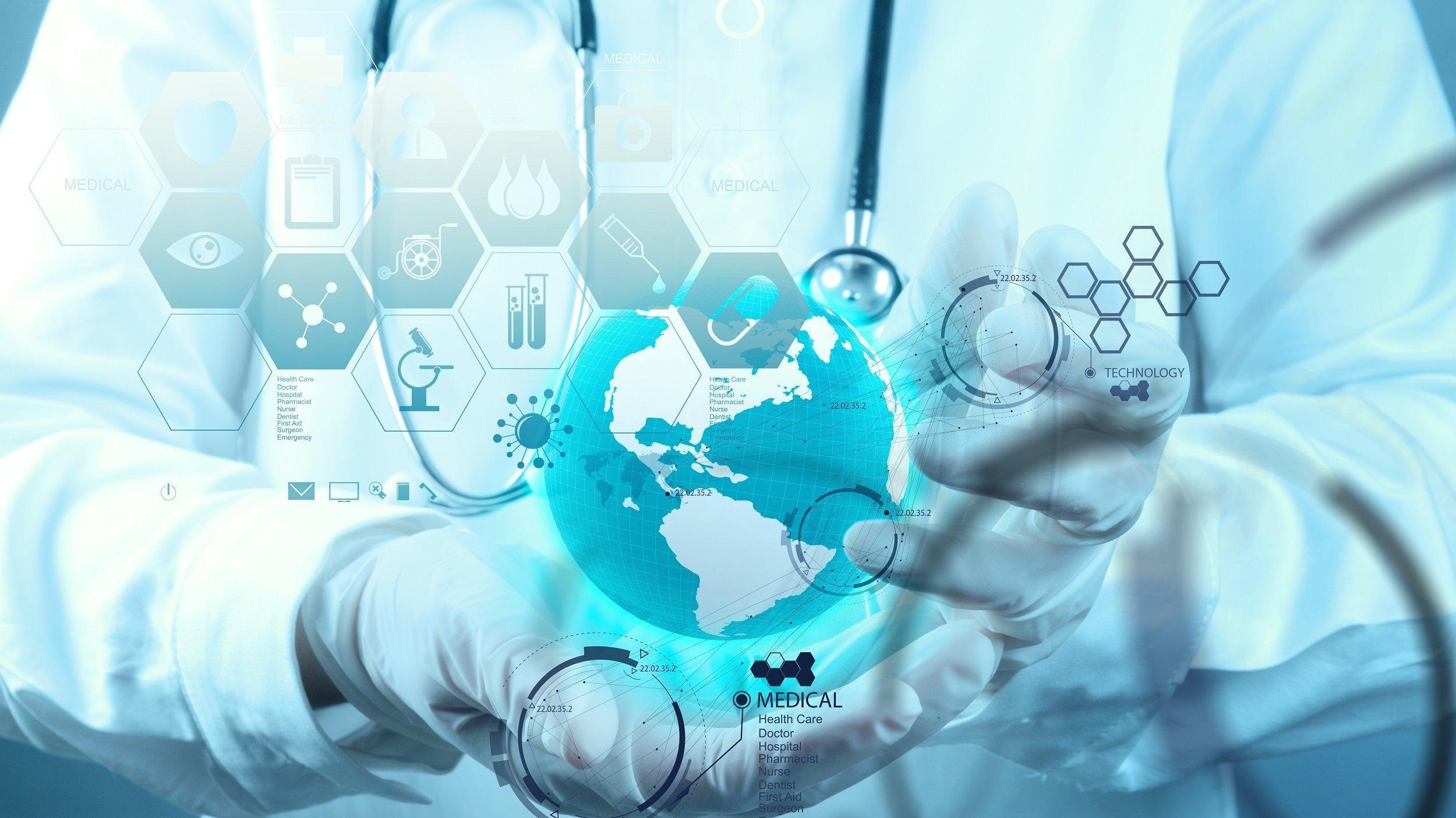 Ein Arzt trägt auf Händen eine symbolische Weltkugel, die von vielen biomedizinischen Symbolen auf einem Computermonitor umgeben ist.