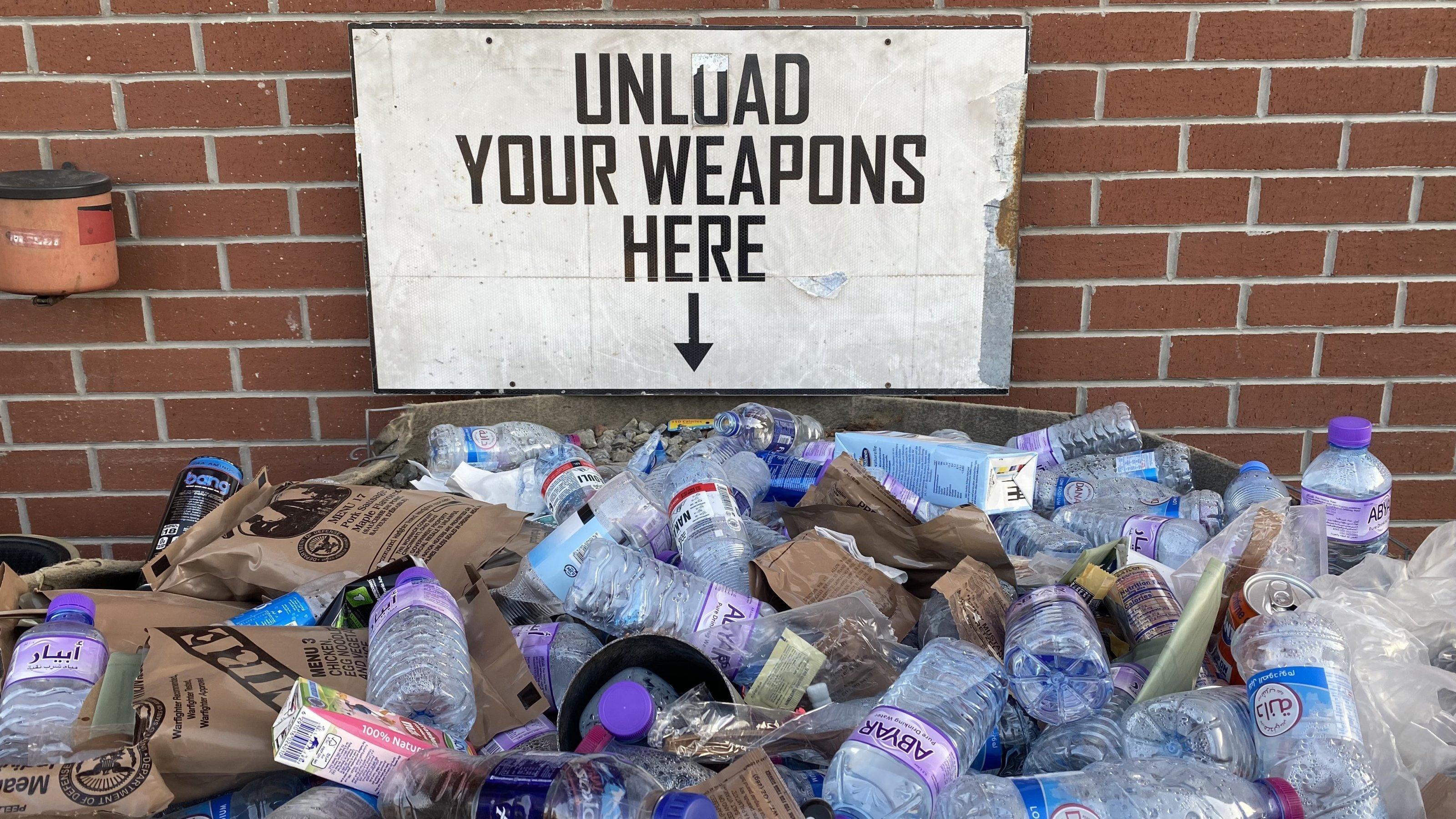 """Unter dem Schild mit der Aufschrift """"Unload your weapons here"""" und der Kiste mit Sand, in die die Patronenhülsen sollen, sind vor allem leere Wasserflaschen zu sehen. Hinweis auf die vielen Zivilisten, die am Flughafen Zuflucht gesucht hatten."""
