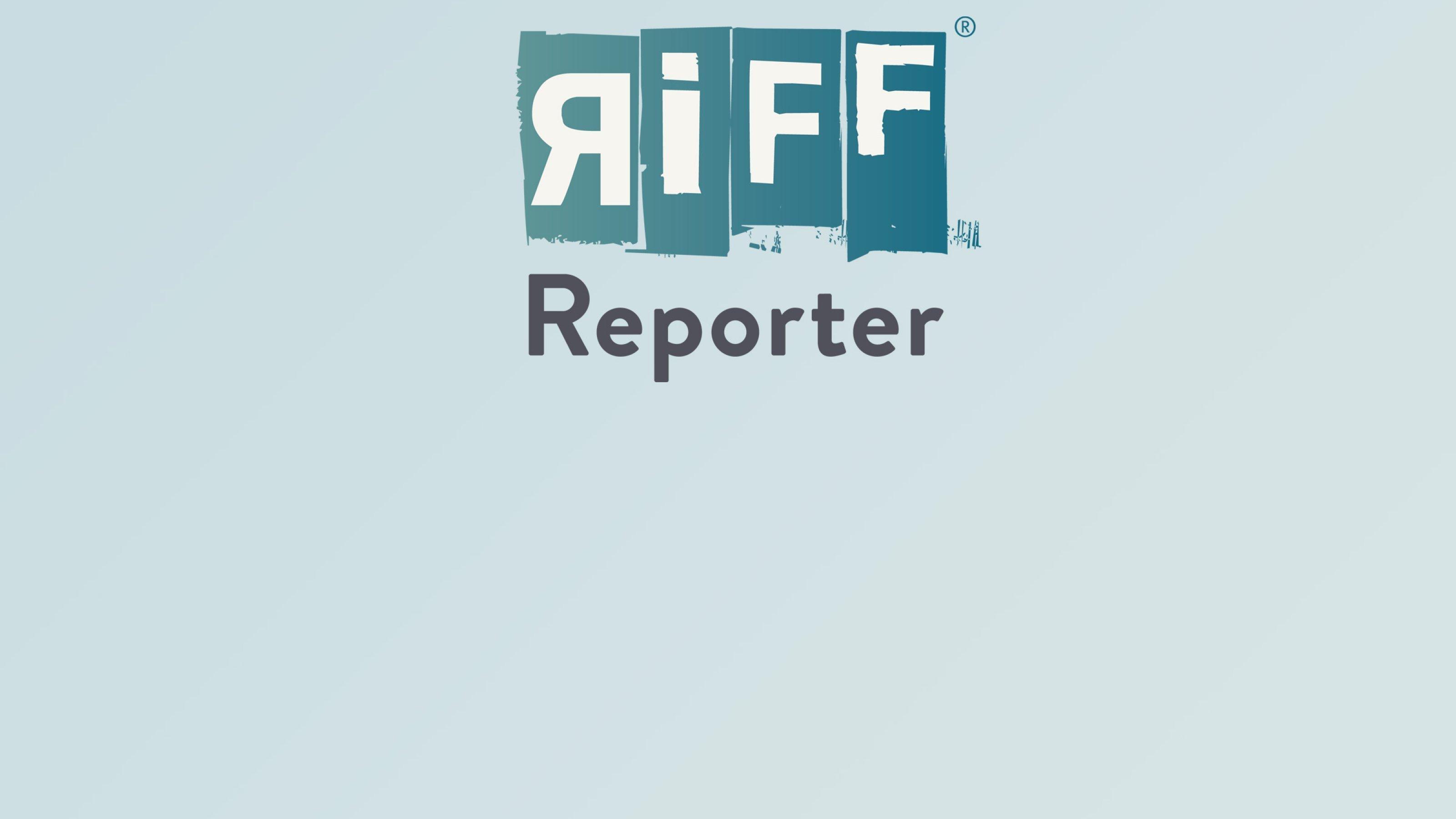 Der Bildbetrachter blickt von einer Anhöhe hinab auf einen blau-grün schimmernden See, der von grünen Bäumen umsäumt ist. Im Hintergrund sind felsige Berge.