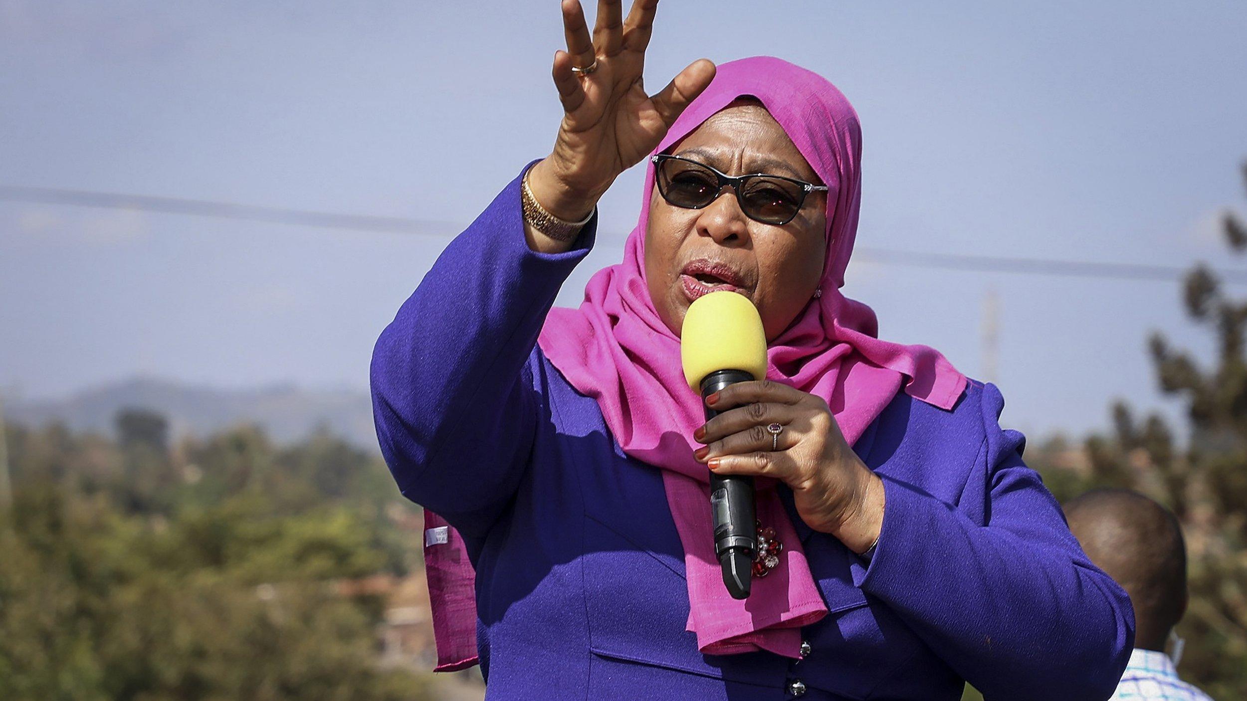 Samia Suluhu Hassan am Rednerpult, eine Hand streckt sie gen Himmel, mit der anderen hält sie das Mikrofon.